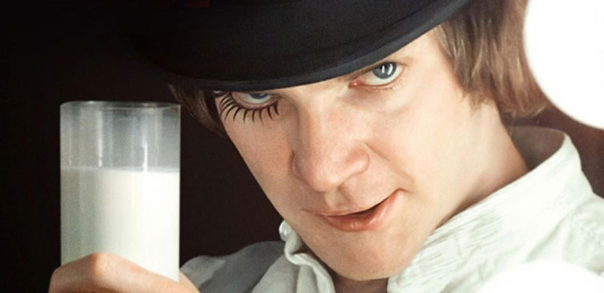 A man in a bowler hat with one false eyelash raises a glass of milk