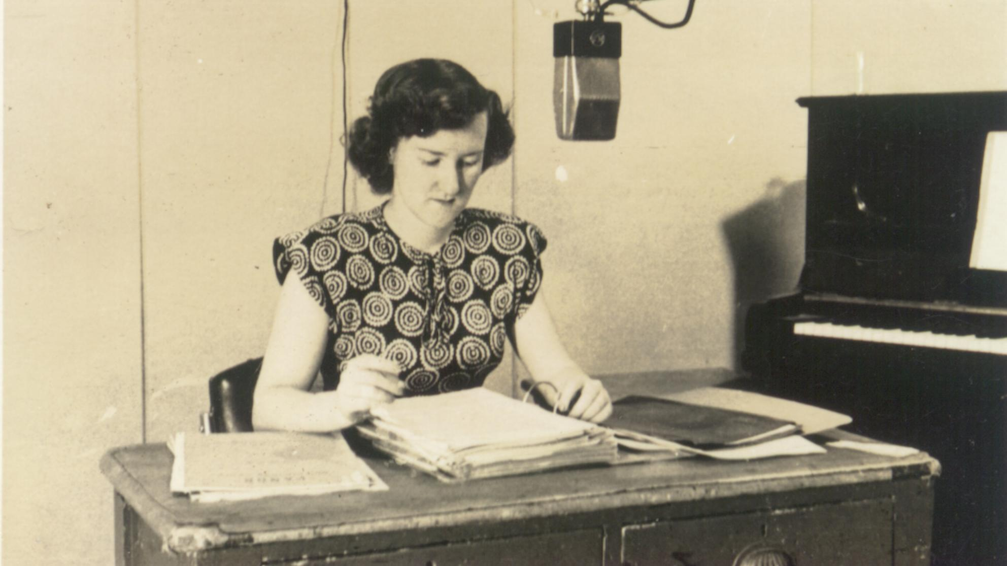 Enid Hogan behind a microphone in a radio studio