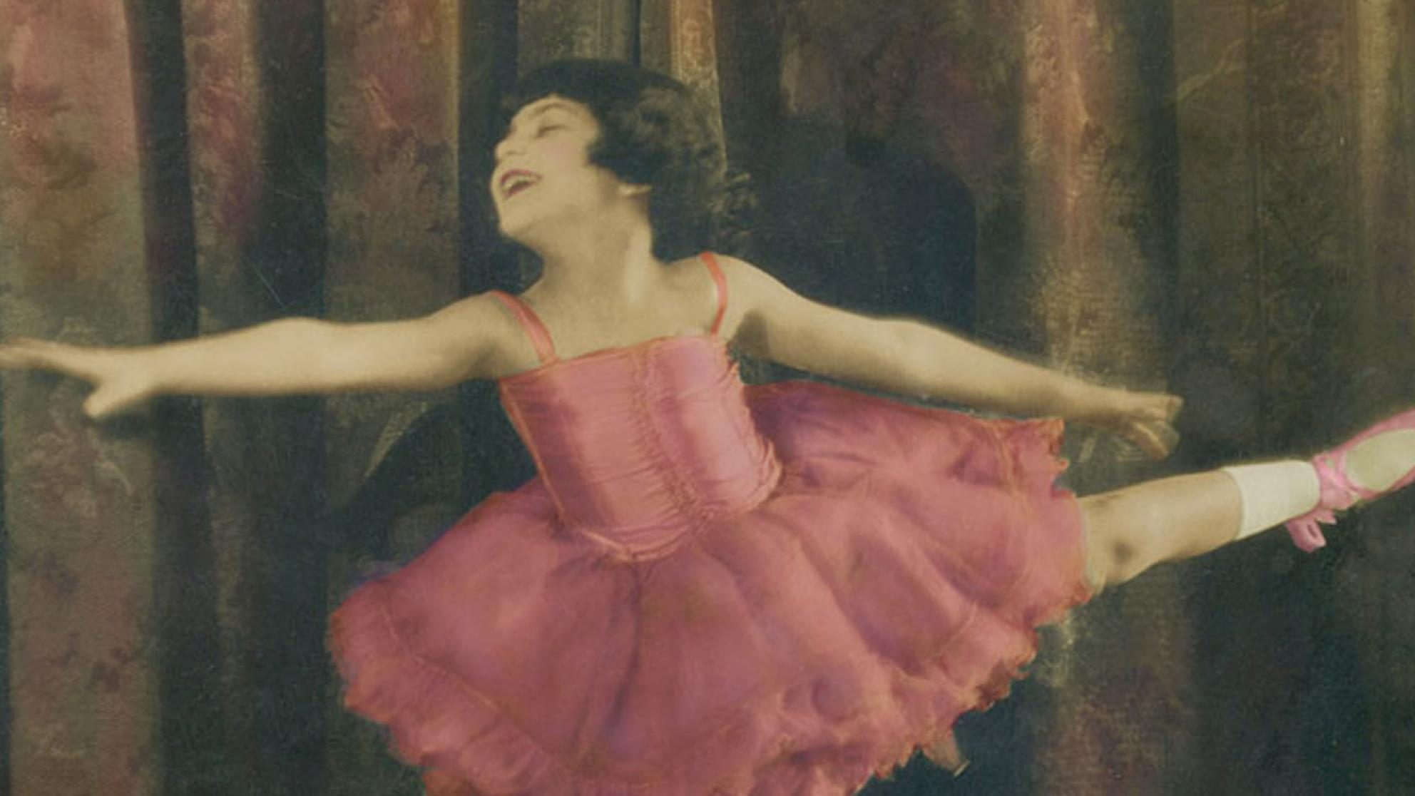 A hand-coloured still of Annette Kellerman as a child. She is dressed in a pink ballet tutu with ballet slippers and is striking a pose with her arms and on leg out.