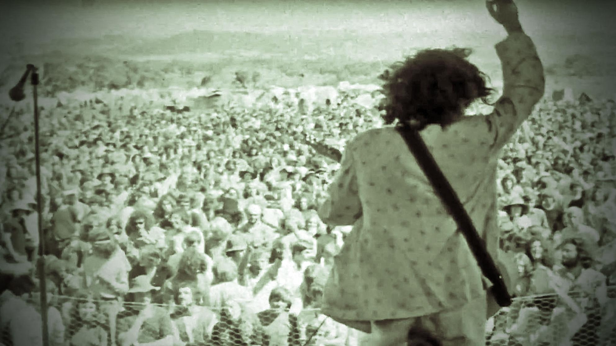 Ross Wilson playing guitar on an outdoor stage with his back to camera, facing a large crowd with his right arm raised, from a screenshot of the film clip for the song Eagle Rock.