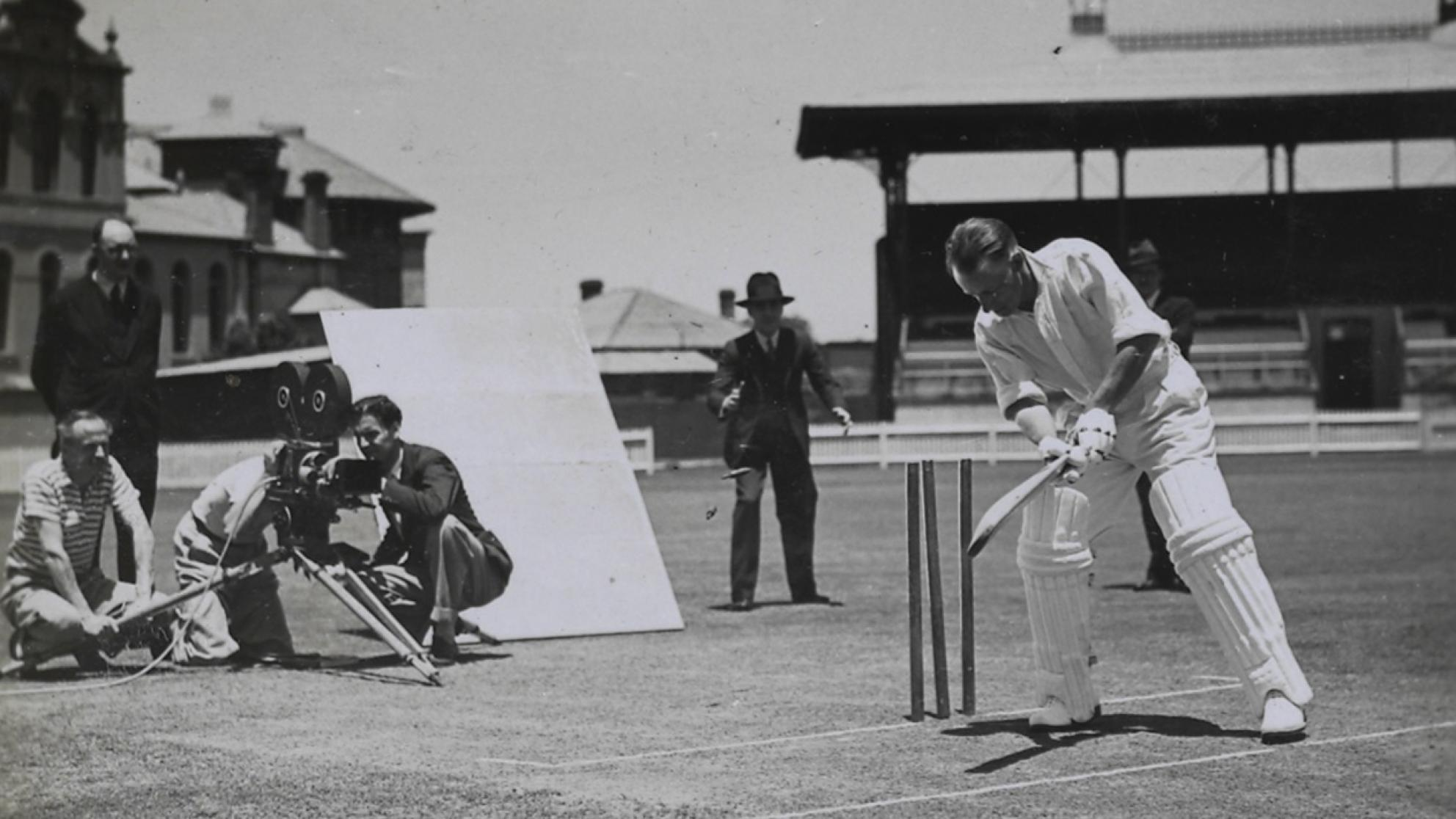Donald Bradman batting in front of wickets while a film crew films him from behind