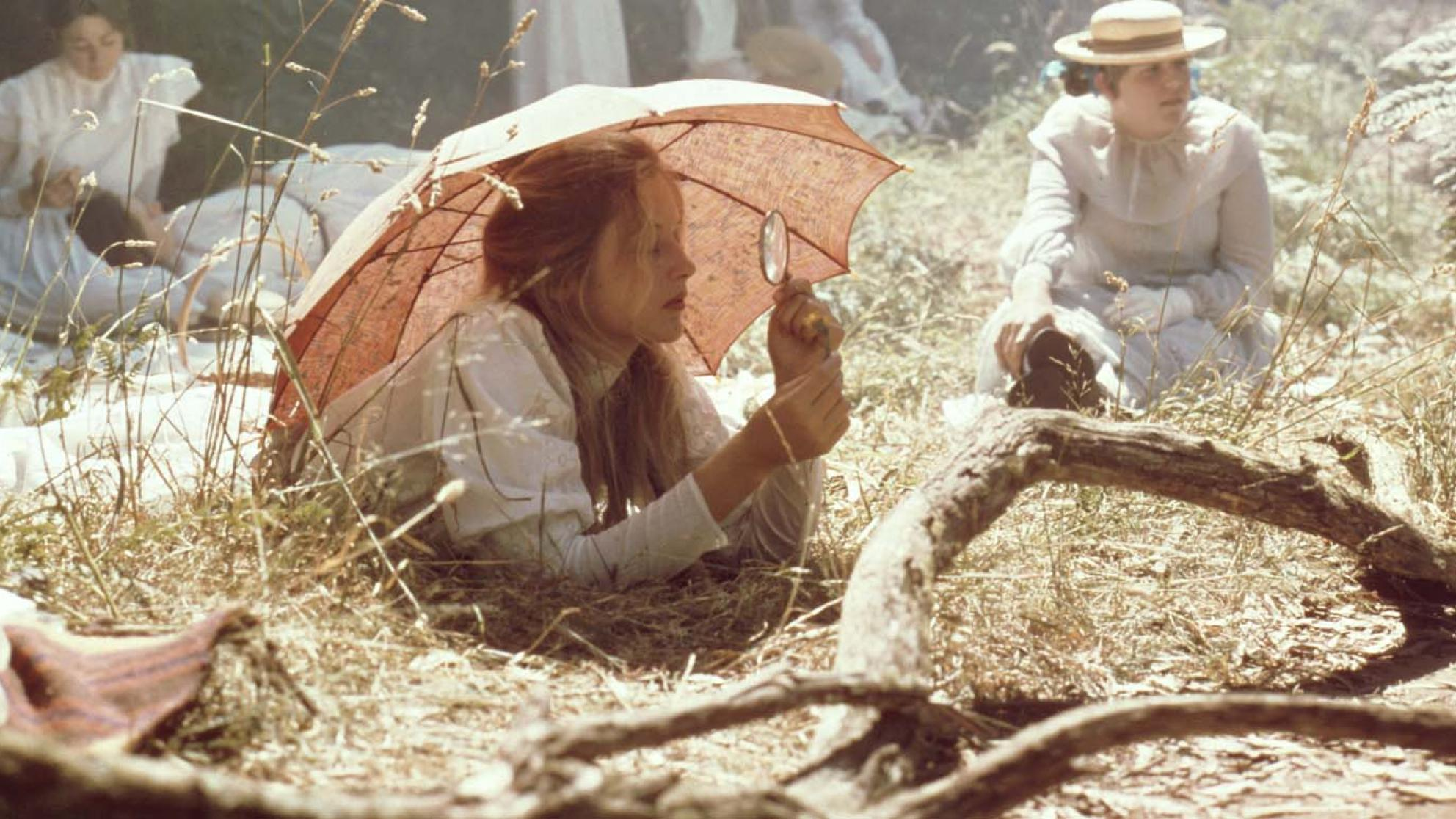 Miranda rests on the grass under a parasol and looks through a magnifying glass in a scene from the film Picnic at Hanging Rock