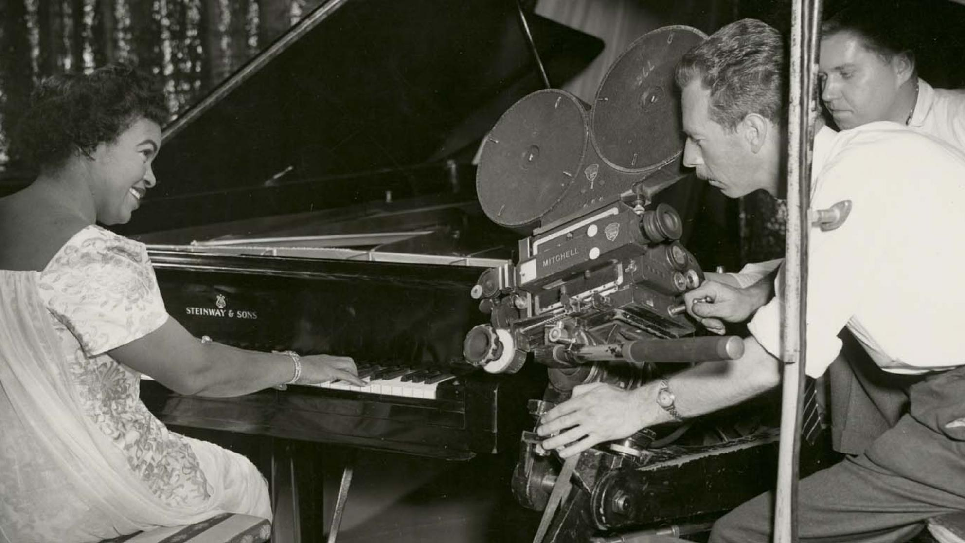 Winifred Atwell playing the piano and smiling while two men film her with a 35mm film camera next to the piano