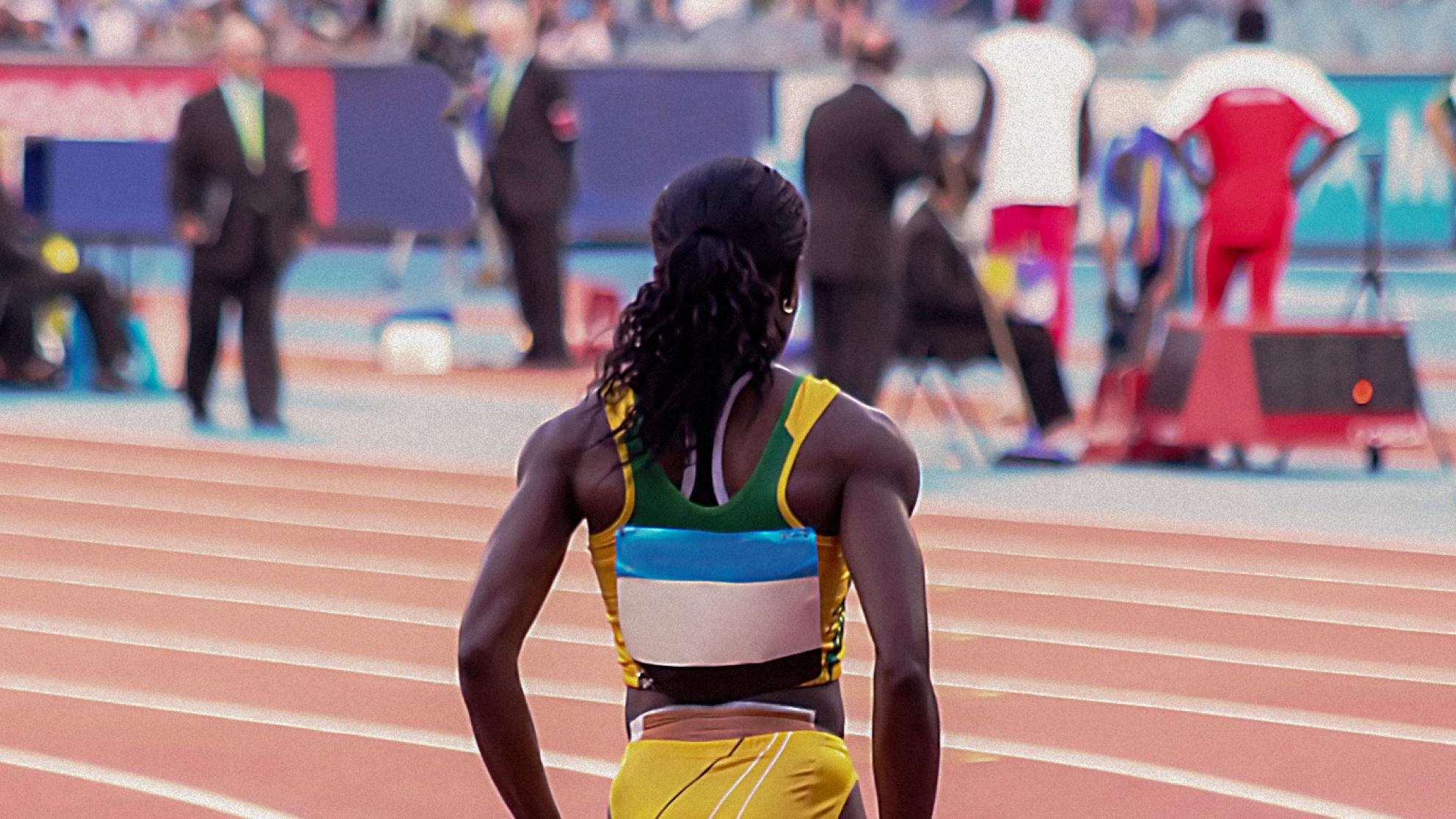 Back view of a female athlete standing on the running track.