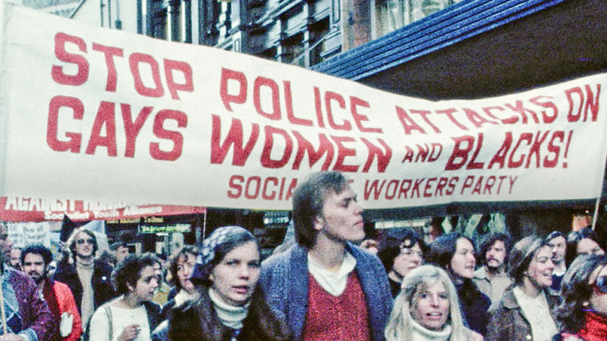 A Sydney protest march in the late 1970s with young people walking under a banner that reads 'Stop police attacks on gays, women and blacks!'