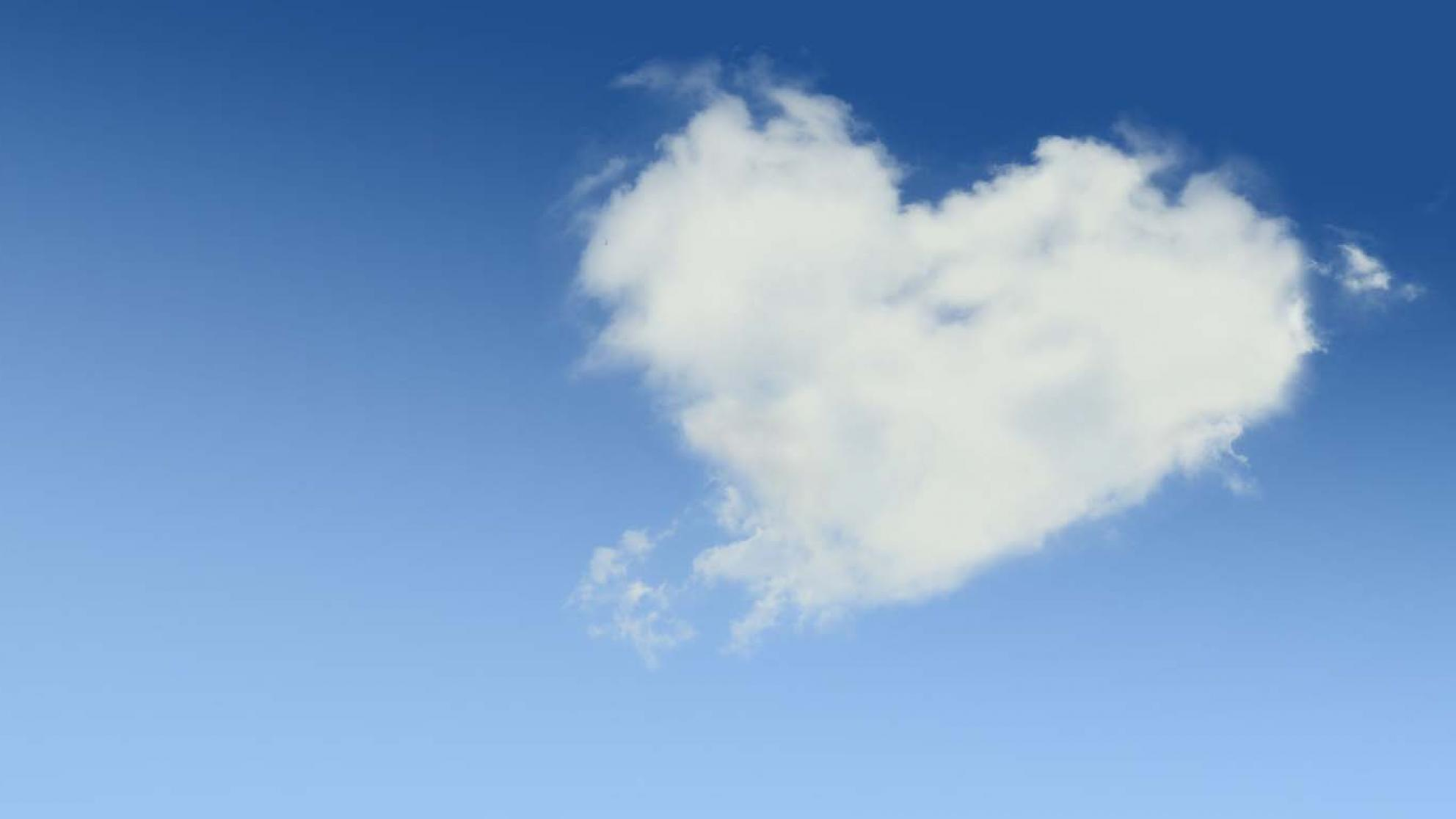 A heart-shaped cloud against a blue sky