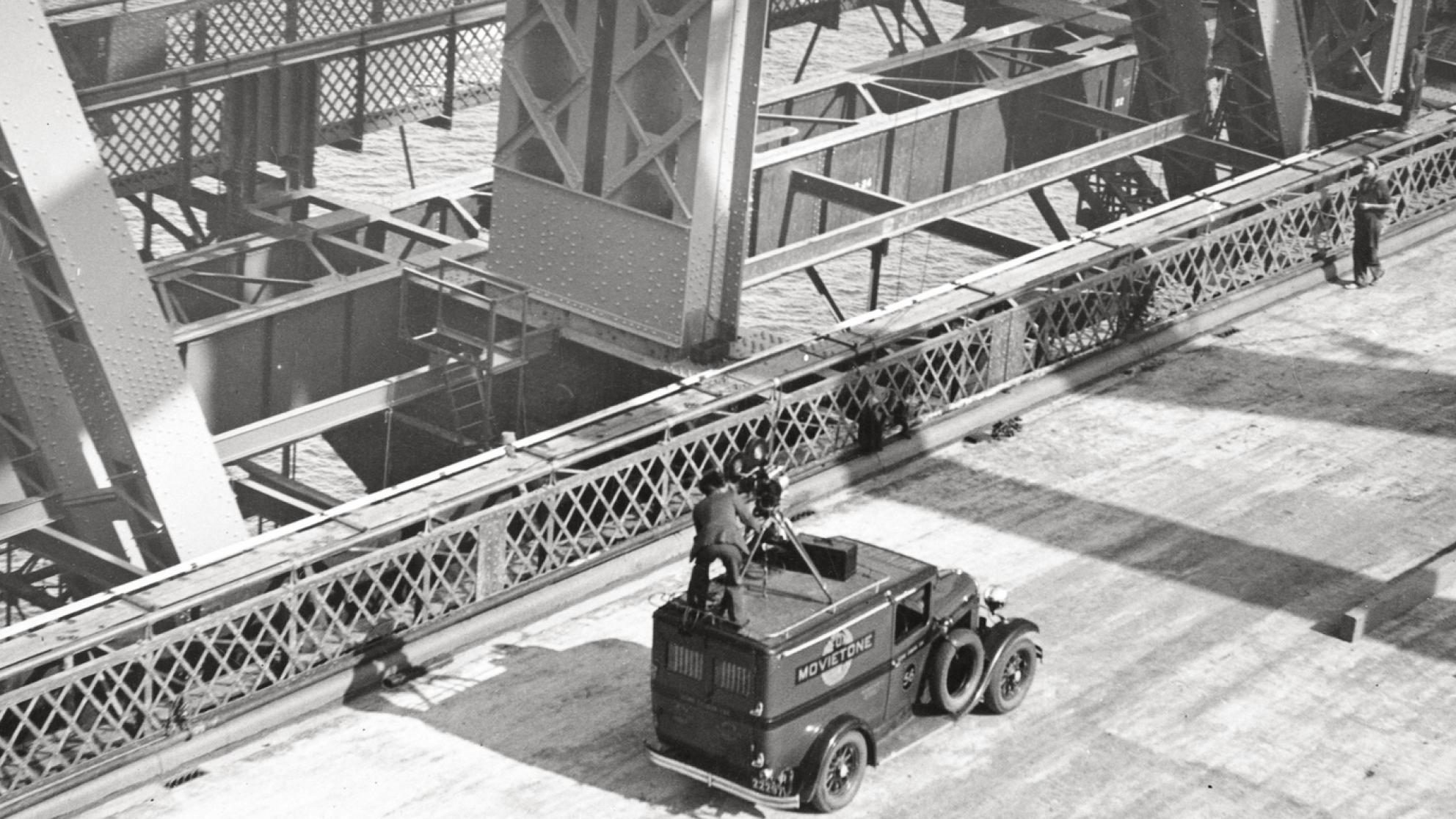 Fox Movietone Productions van with a man standing on top operating a camera. The van is on the deck of the newly-constructed Sydney Harbour Bridge.