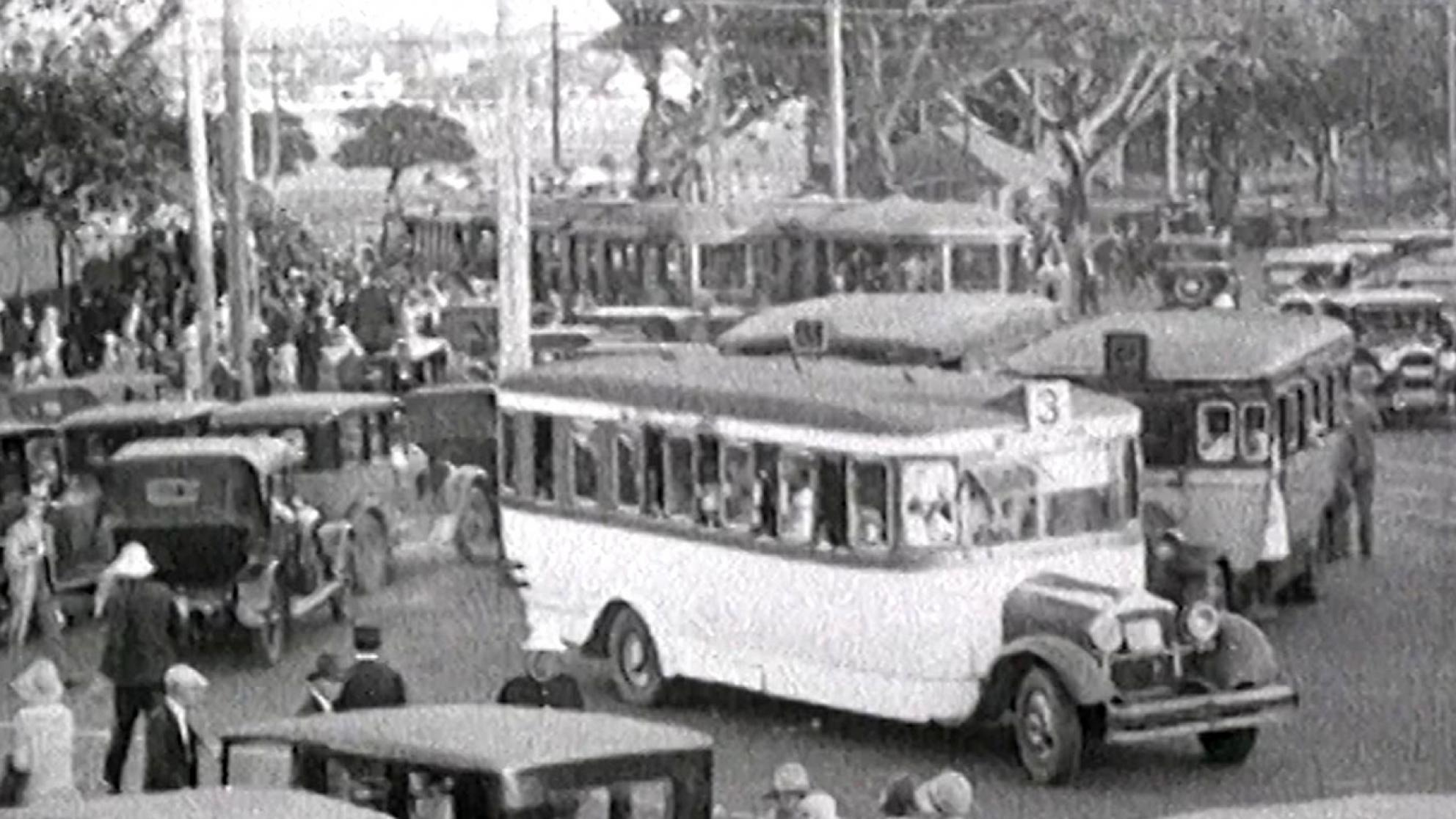A picture from 1928 of ordered traffic chaos. Buses, trams and automobiles all crowd Anzac Parade Junction with fig trees in the background.