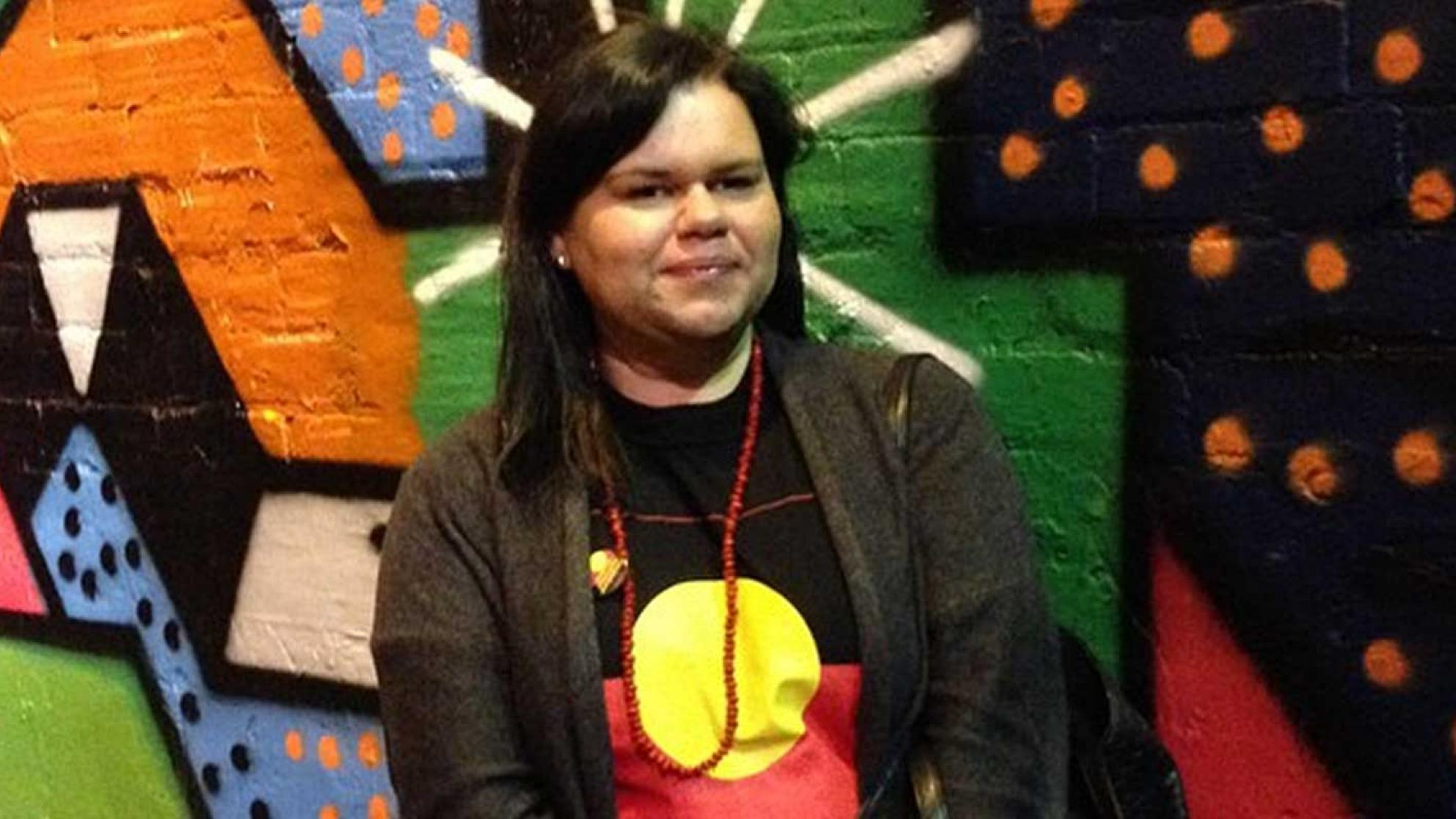 Tasha James standing in front of a colourful wall and wearing shirt bearing the Aboriginal flag