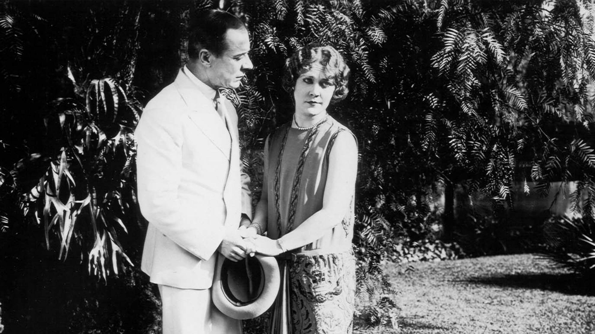 A man holds hands with Louise Lovely in a garden in a scene from the silent film Jewelled Nights.