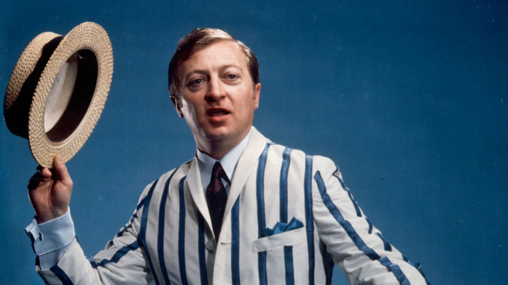 Graham Kennedy wearing a striped jacket and holding a straw boater hat in a promo shot for GTV 9.