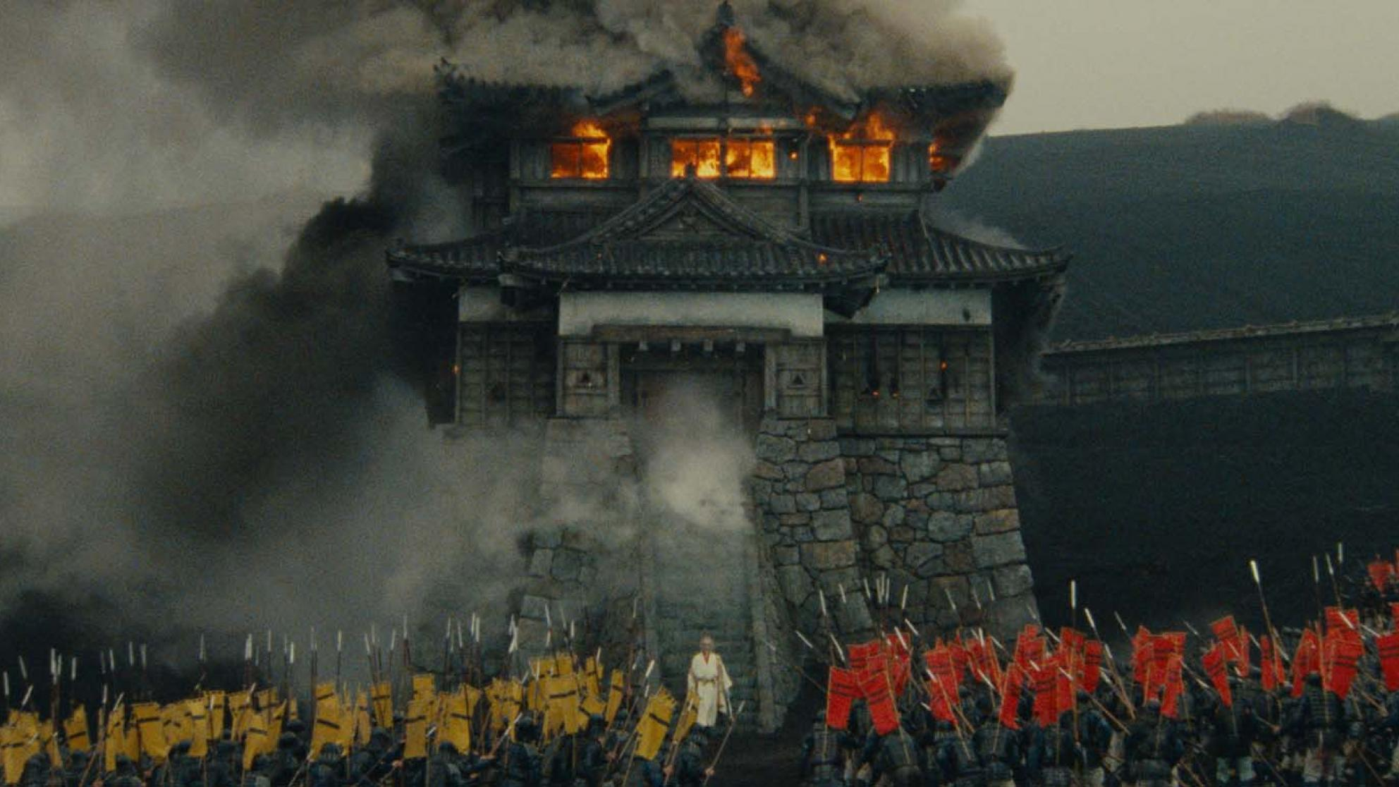 Film still from RAN of a Japanese castle on fire surrounded by an army.