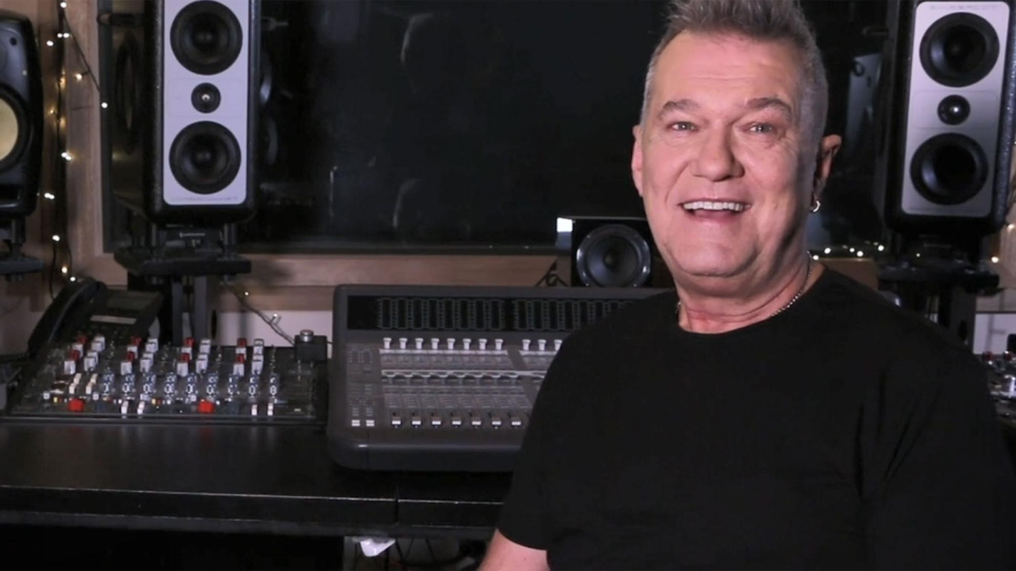 Singer Jimmy Barnes pictured from the chest up, in a black t-shirt and sitting in front of a mixing deck in a recording studio.