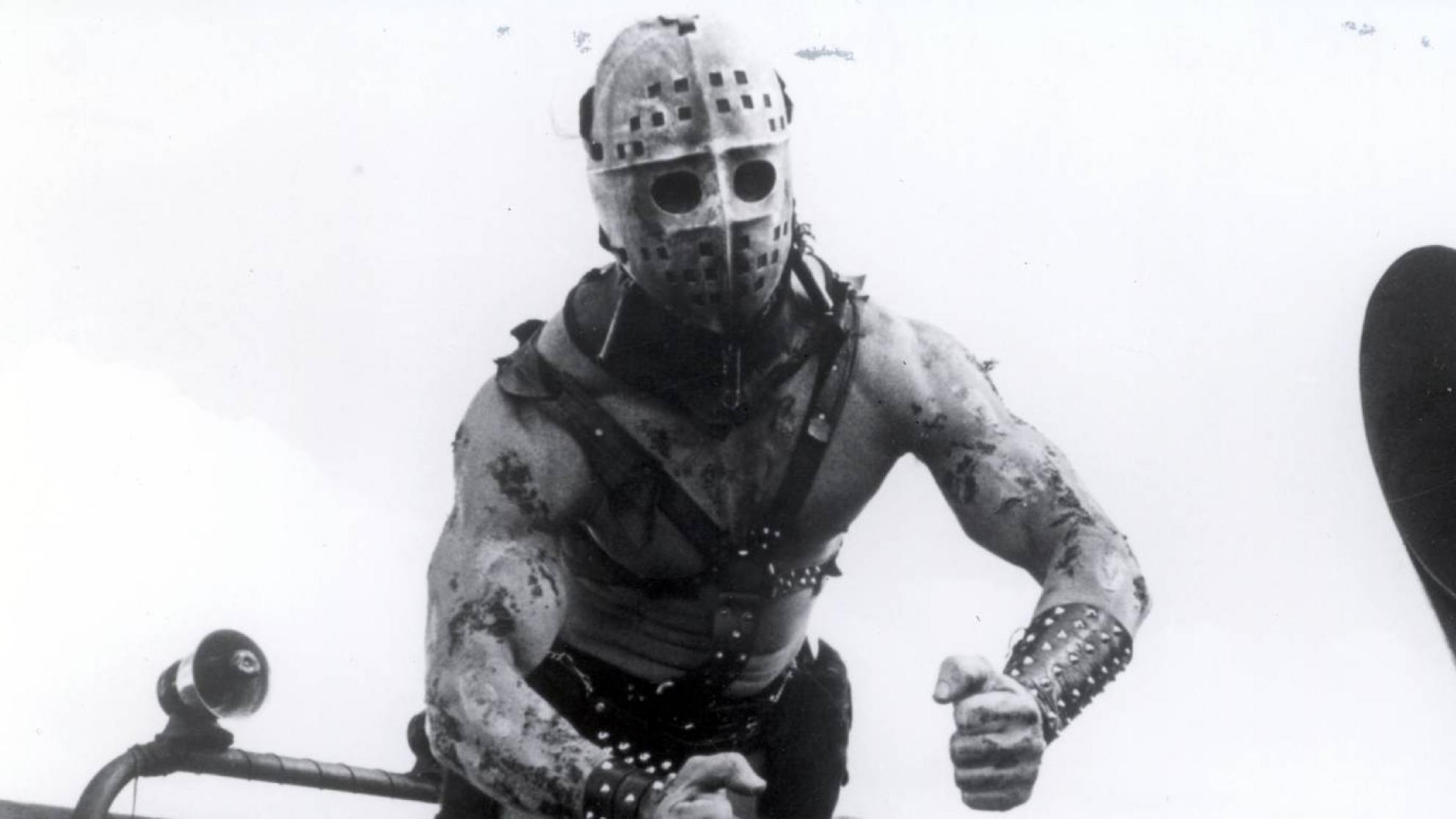 Mad Max 2 villain Humungus strikes a muscular pose with his face covered by a hockey mask
