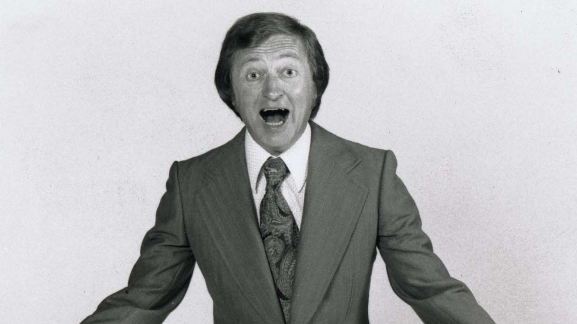 A 1970s publicity shot of Graham Kennedy wearing a suit and exclaiming at the camera.