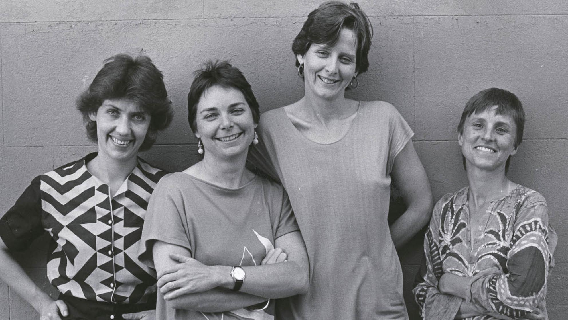 Filmmakers Margot Nash, Megan Mcmurchy, Jeni Thornley and Margot Oliver standing in front of a wall smiling for the camera.