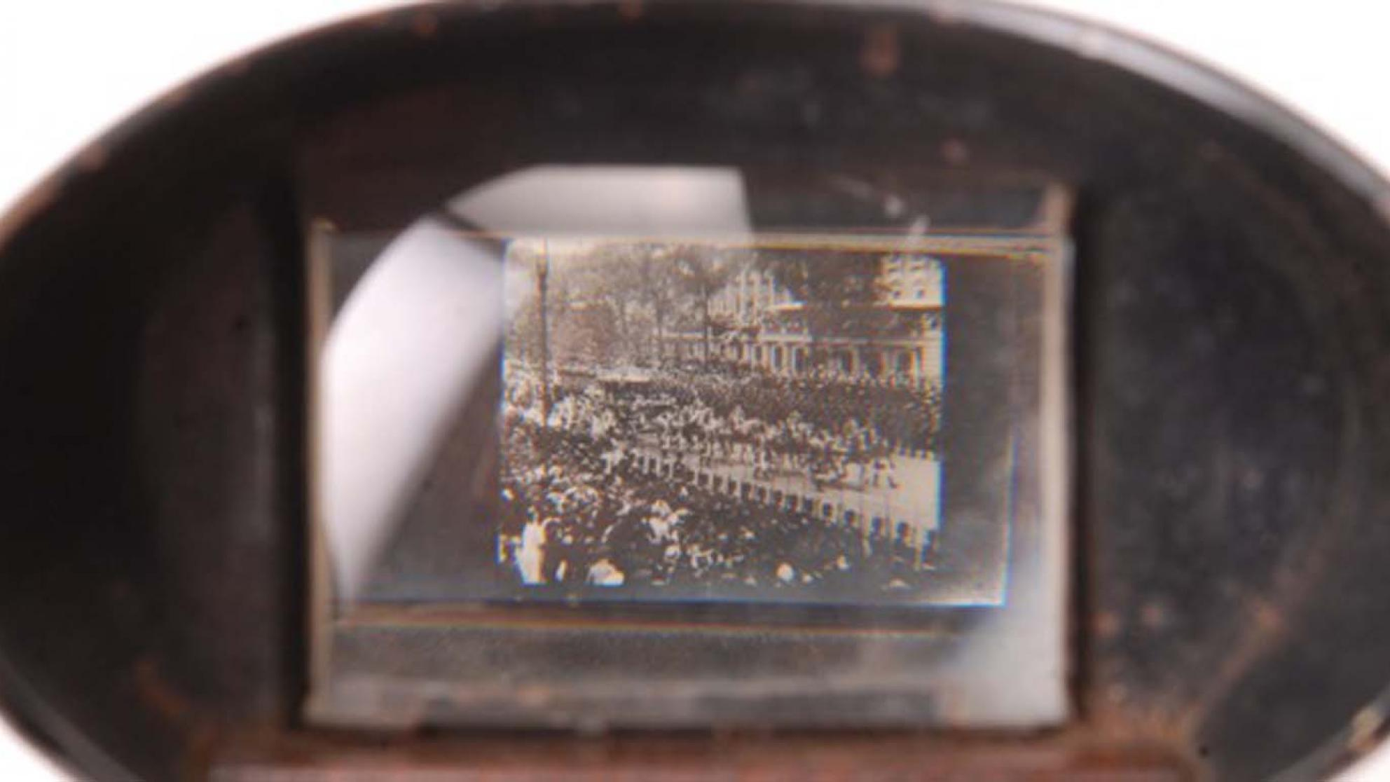 Looking through the viewing lens of a kinora at an image of a crowd scene.