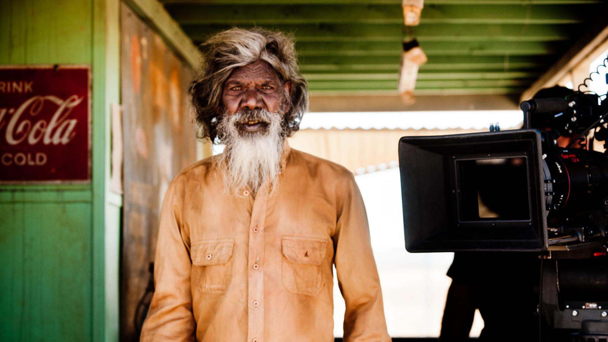 David Gulpilil on the set of Satellite Boy with a film camera beside him. He is looking directly at the camera.
