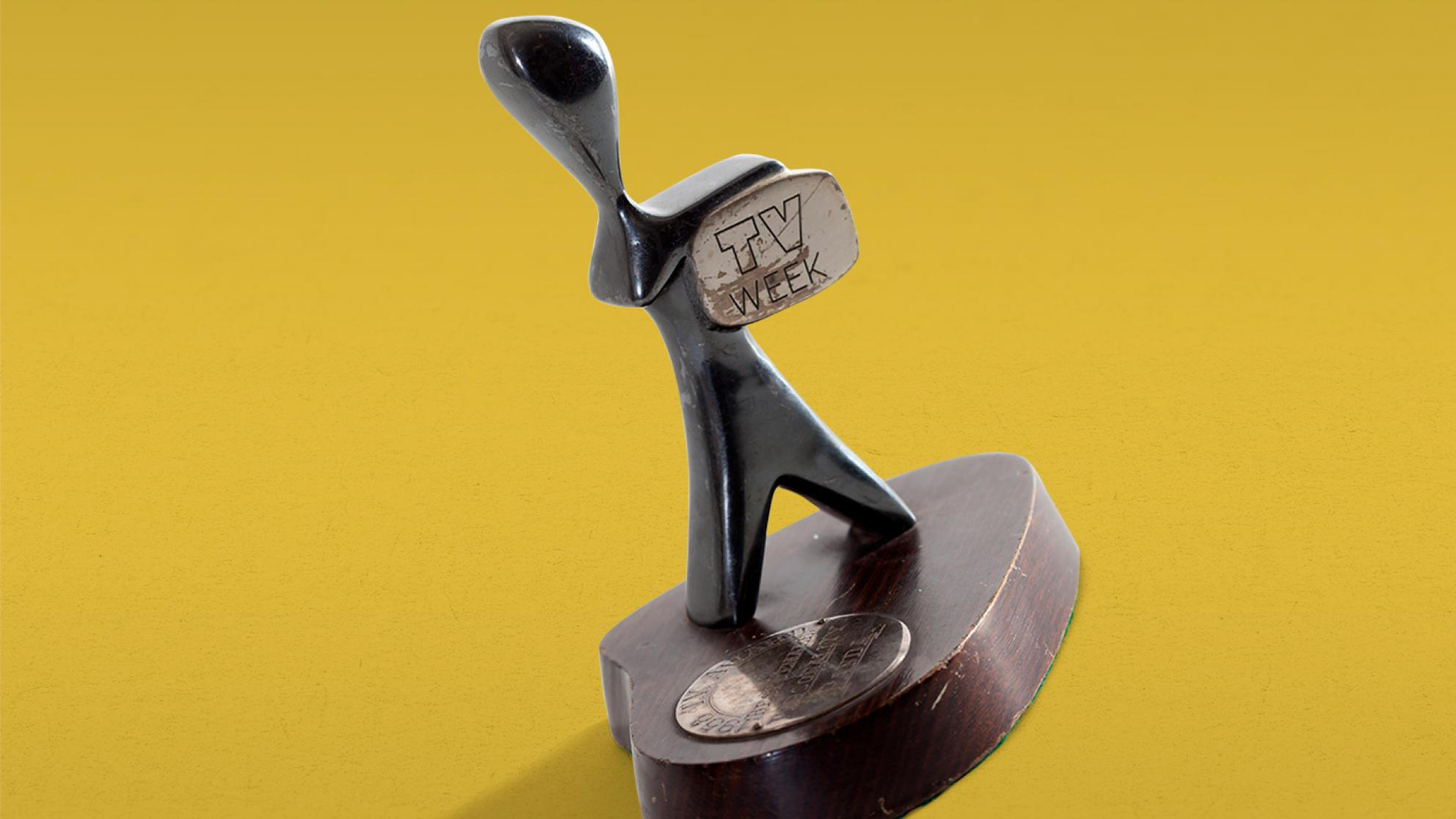A TV Week Logie Award, made up of a small silver statuette in the shape of a man holding a television. The statuette sits on a round wooden base with a metal disc with words engraved on it.