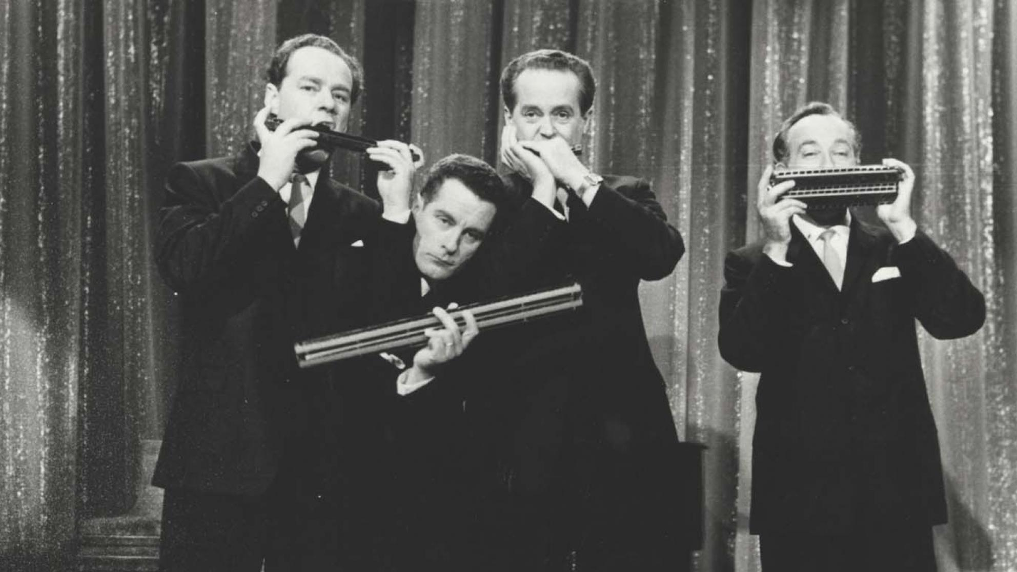 The members of the Horrie Dargie Quintet pose in front of a curtain, each member holding a harmonica