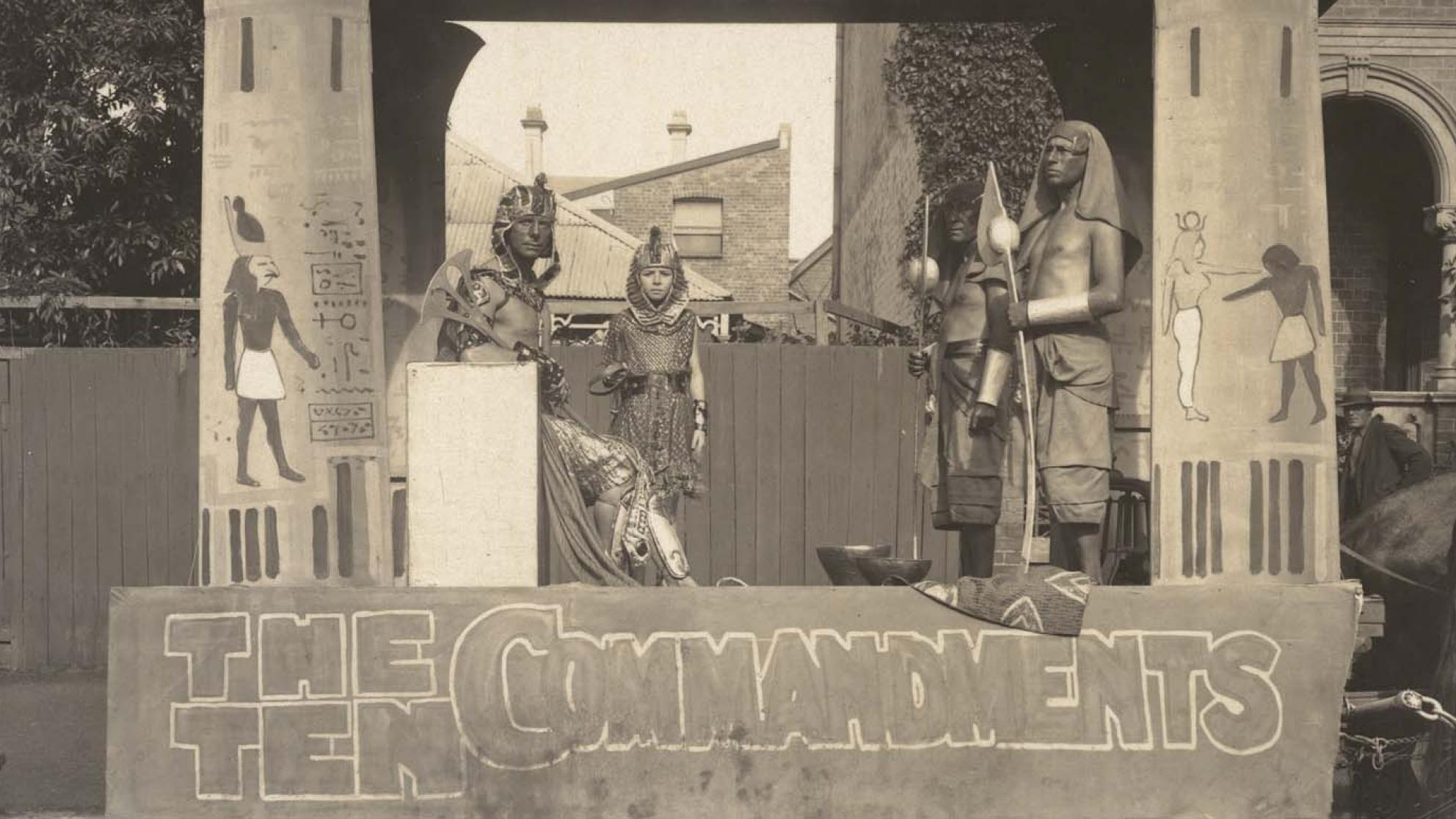 Four actors in costume pose on a horse-drawn trailer promoting The Ten Commandments in 1925