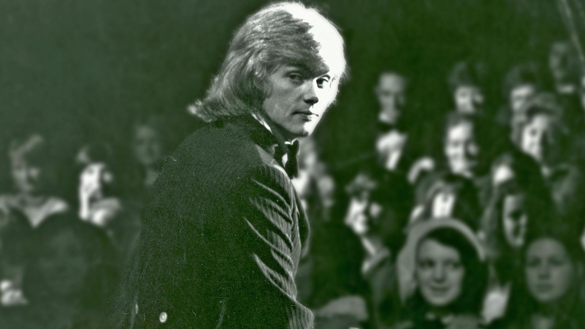 John Farnham sitting on stage in front of an audience, looking back over his right shoulder at the camer.