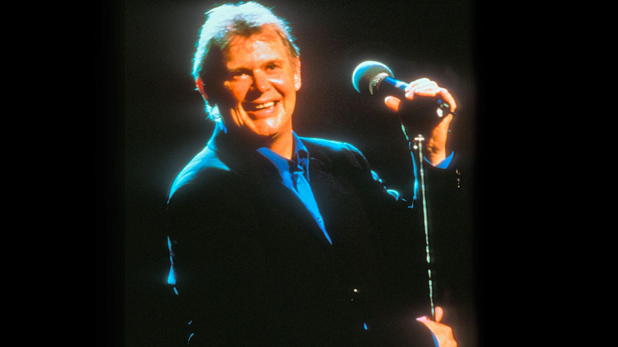 Singer John Farnham, circa late 1990s or early 2000s, pictured from the waist up wearing a black jacket and blue collared shirt, standing on a stage and holding on to a microphone stand. He's smiling at the camera.