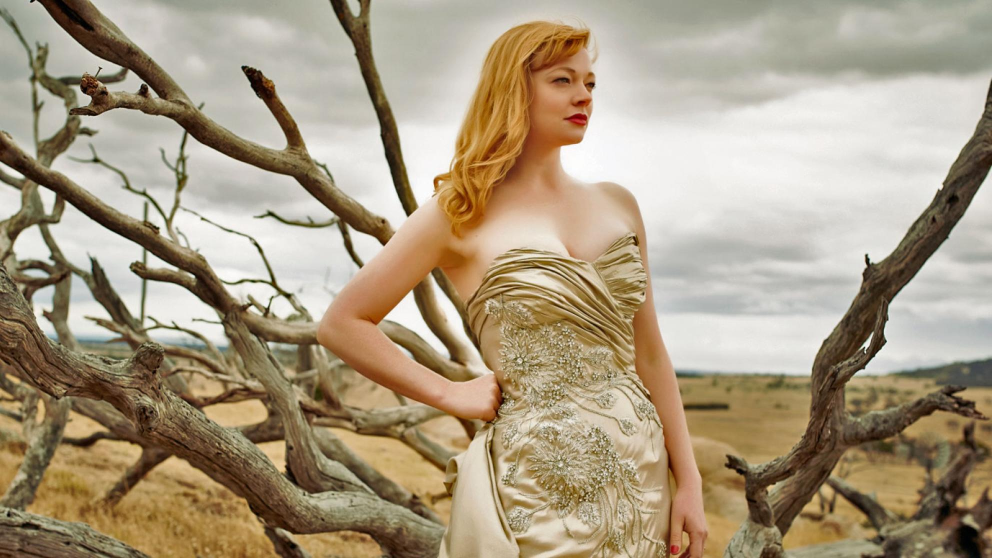 Actress Sarah Snook in a publicity shot for The Dressmaker, wearing a fitted, champagne-coloured, beaded gown and standing in front of some bare tree branches. In the distance you can see a brown, dusty plain and grey, cloudy sky.
