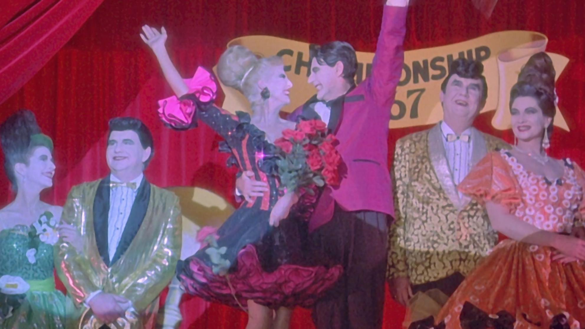 Strictly Ballroom flashback scene three couples dressed overly garishly in ballroom dancing costumes