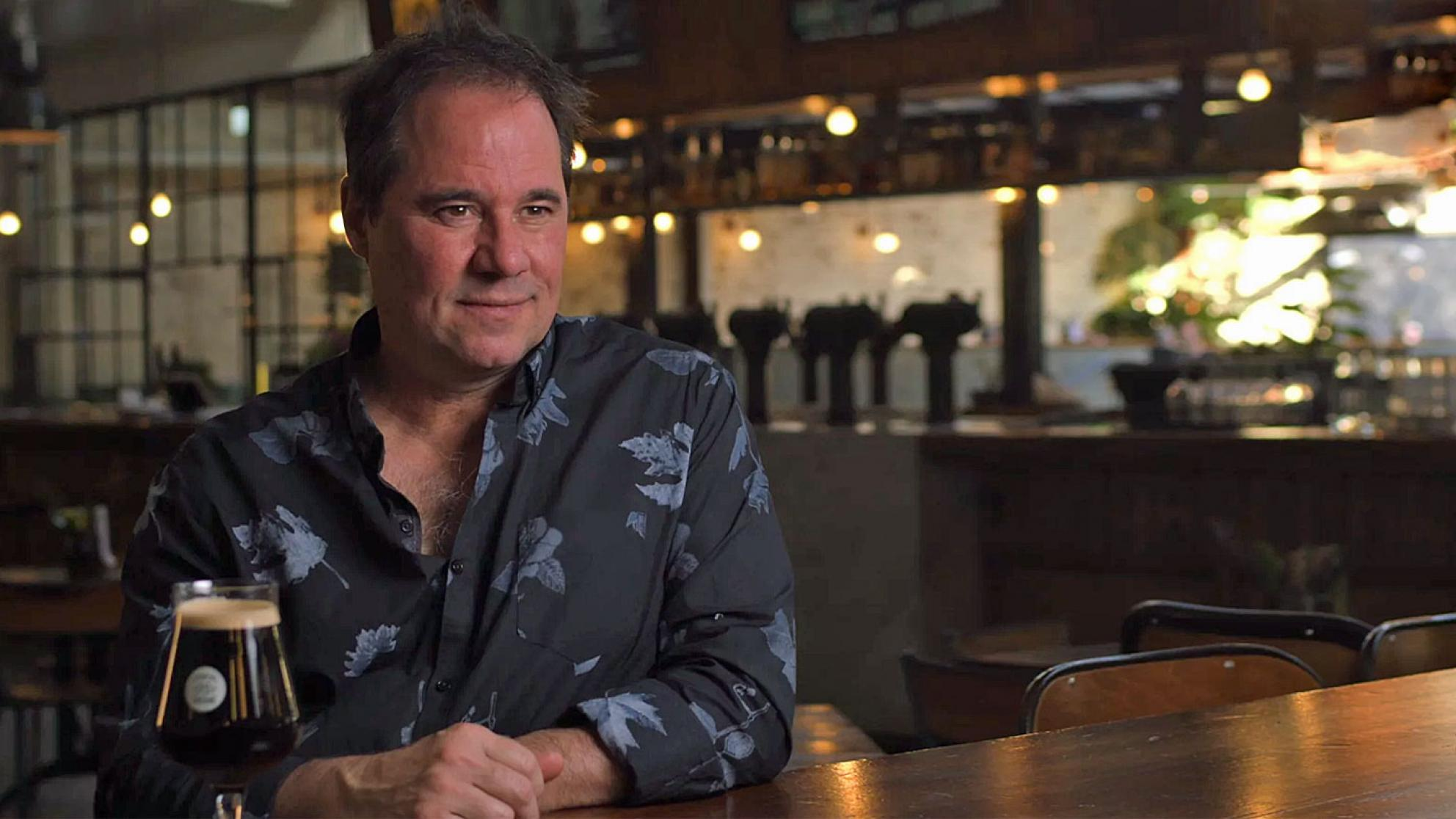 Waist-up shot of actor Paul Mercurio sitting at a restaurant table with a bar in the background.