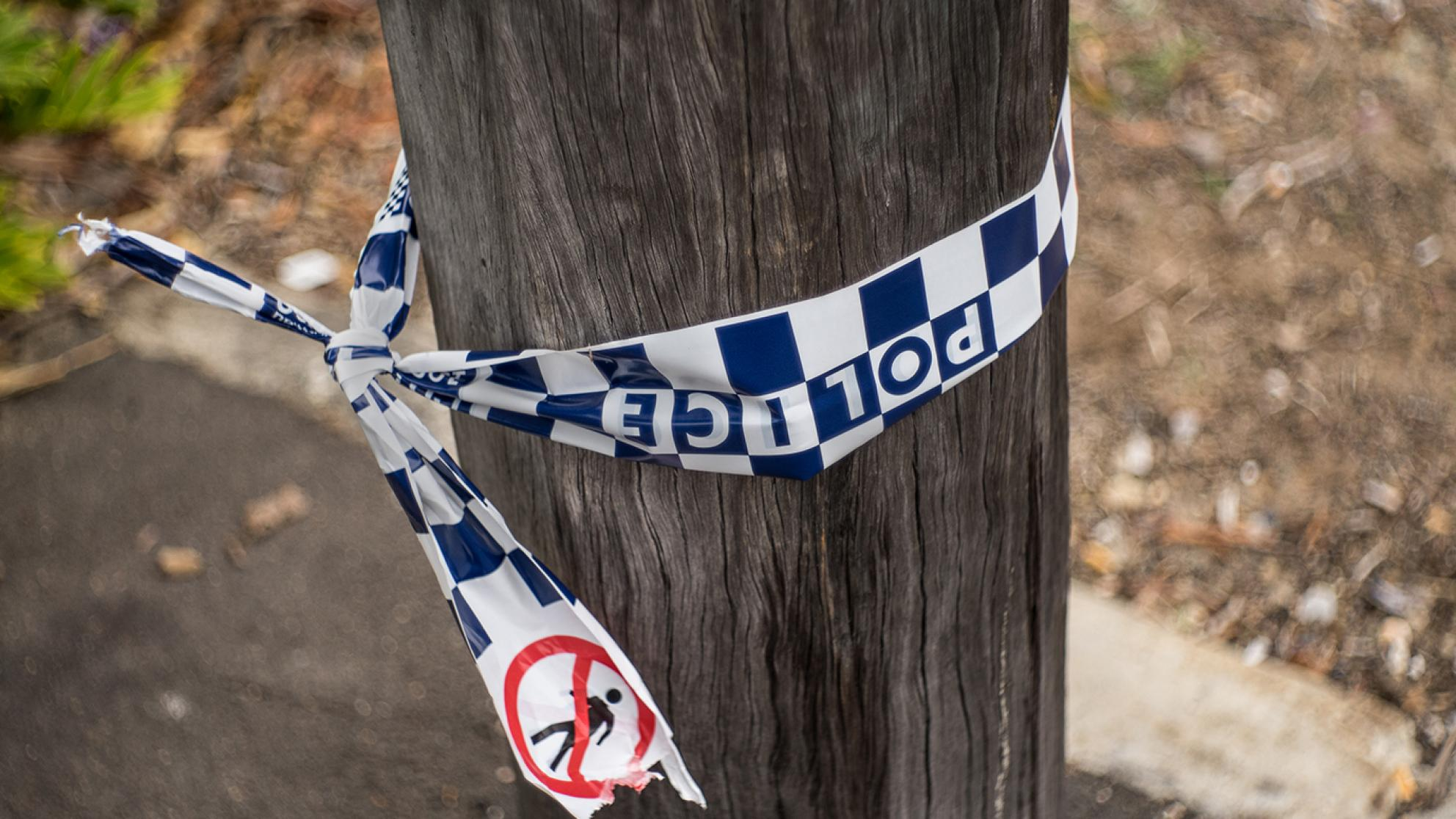 A section of a telegraph pole on a sidewalk with some blue and white chequered police tape tied around it.