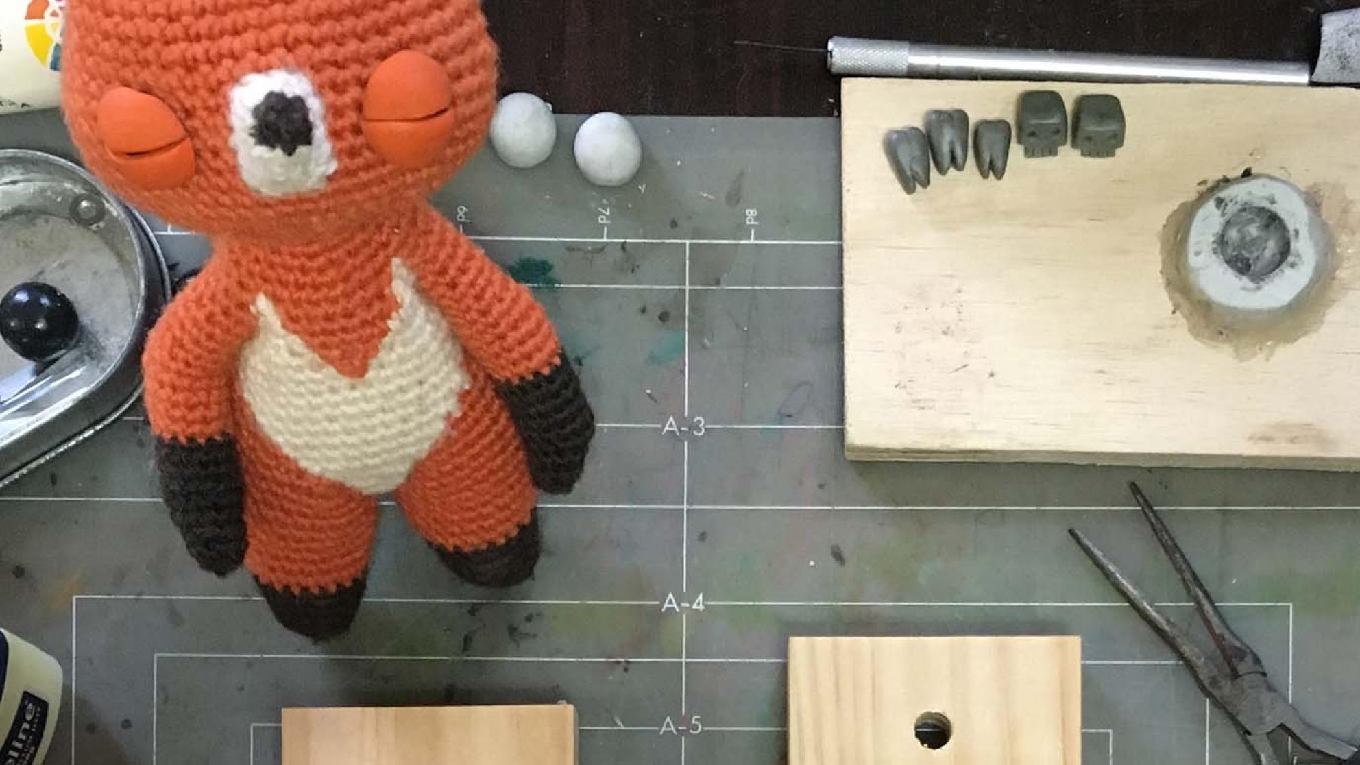 A crocheted animal created for an animated film sits on a workbench awaiting completion