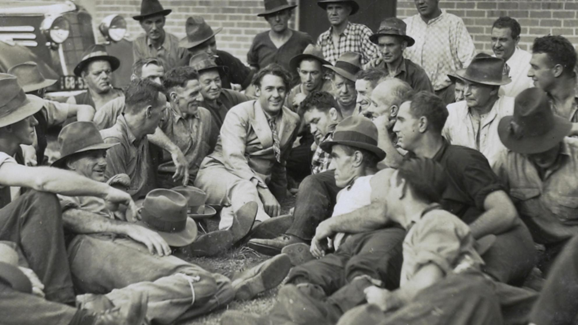 Actor Charles Farrell reclines on the ground surrounded by a crowd of men.
