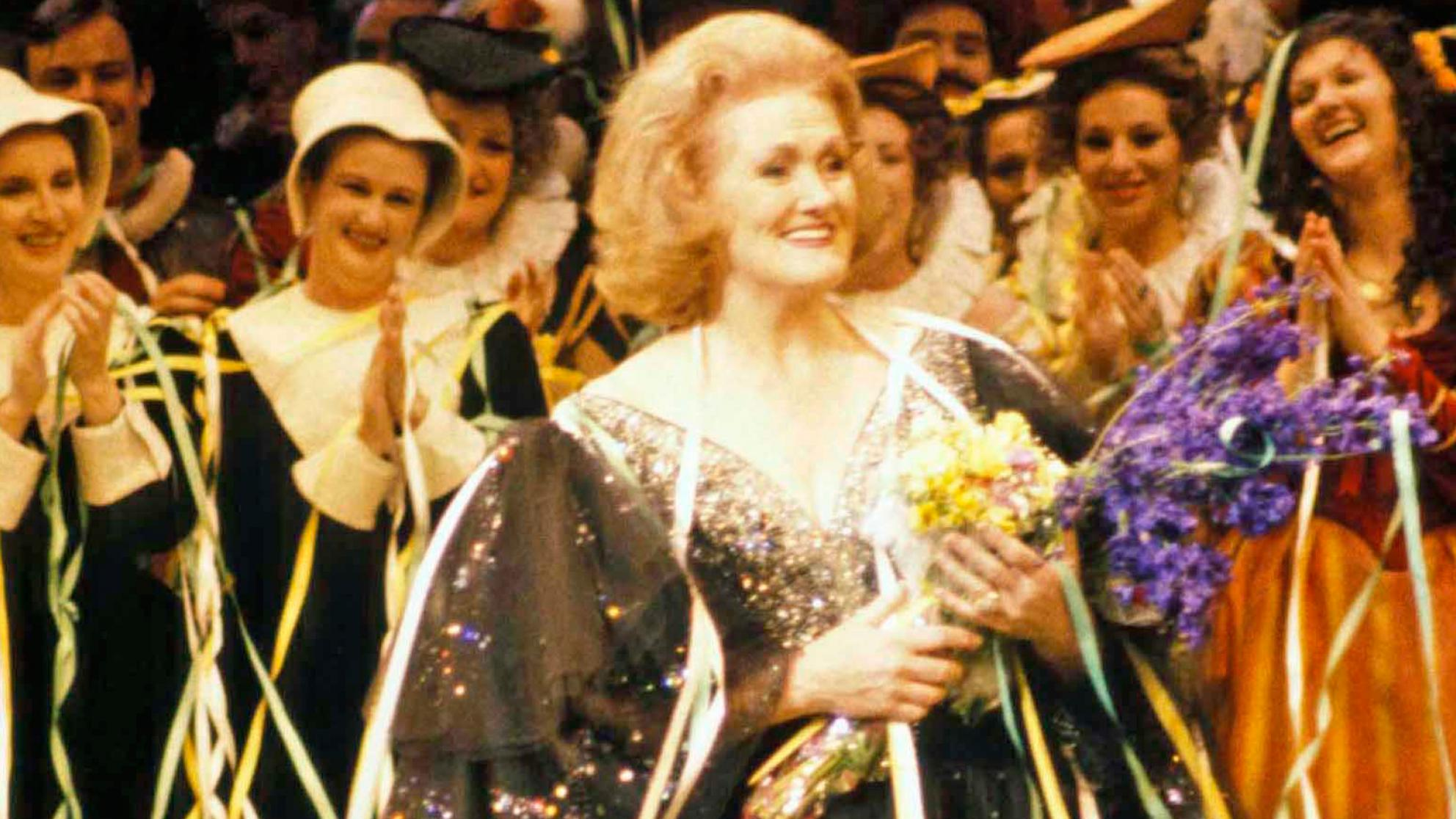 Dame Joan Sutherland on stage holding flowers with the cast applauding her.