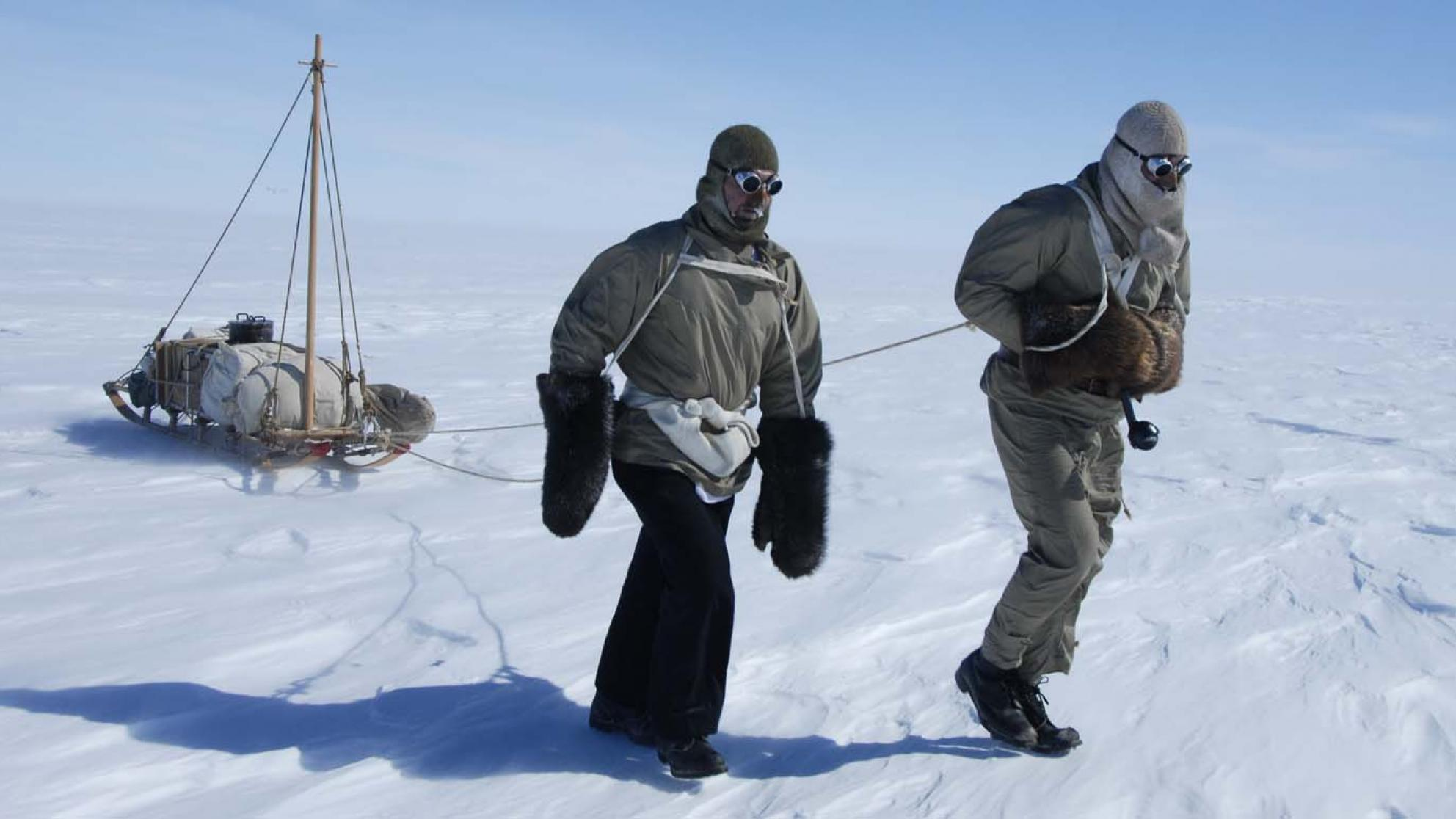 Tim Jarvis and John Stoukala pulling a sledge across the snow in Antarctica for a documentary retracing Mawson's expedition