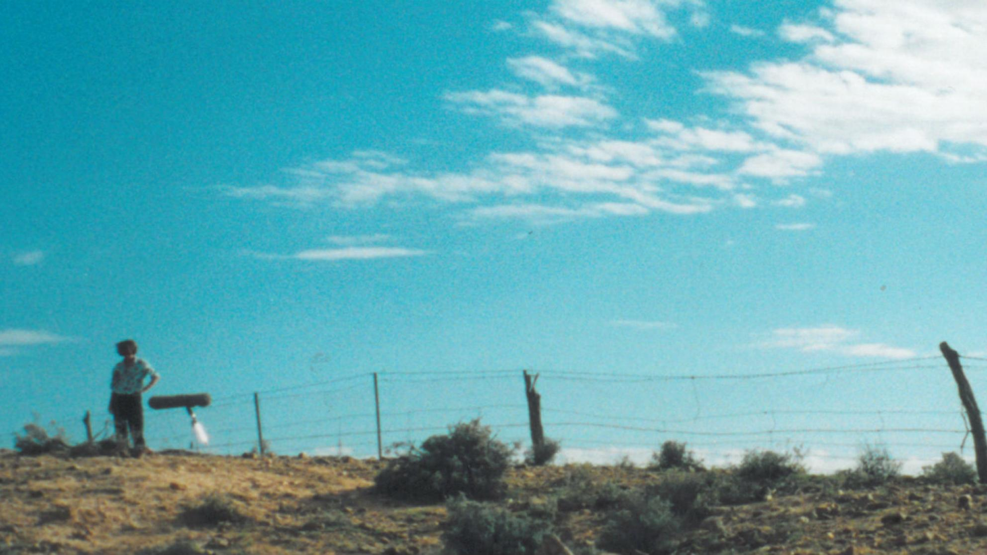 Bronwyn Murphy photographed near fence from a distance with blue sky in the background during filming of Rabbit Proof Fence