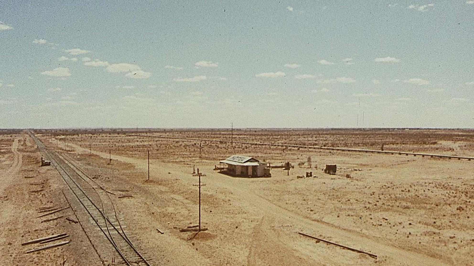 An aerial shot of a hotel and railway line in a vast expanse of outback, in a scene from the 1971 film Wake in Fright