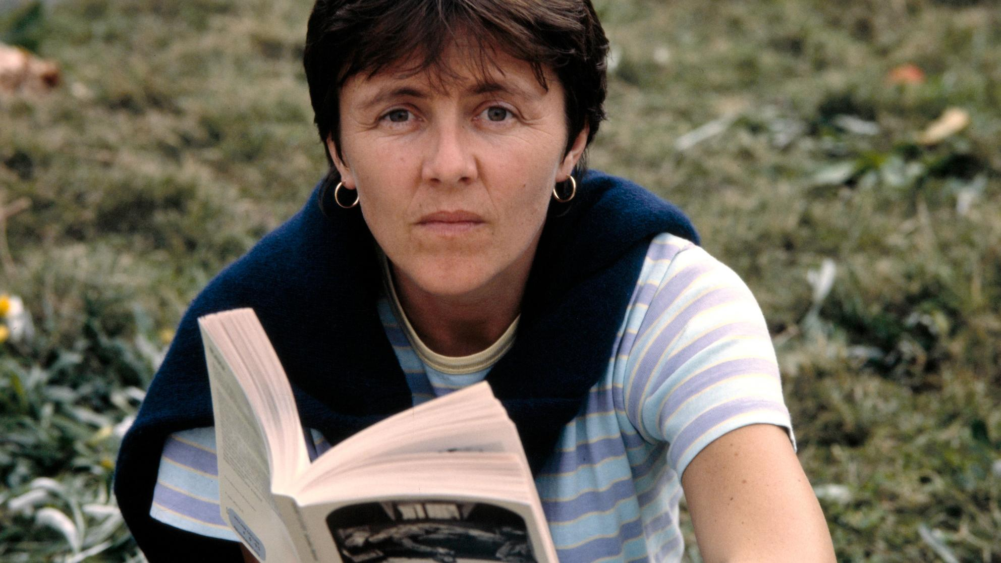 Helen Garner sitting in the ground, look at the camera and holding an open book