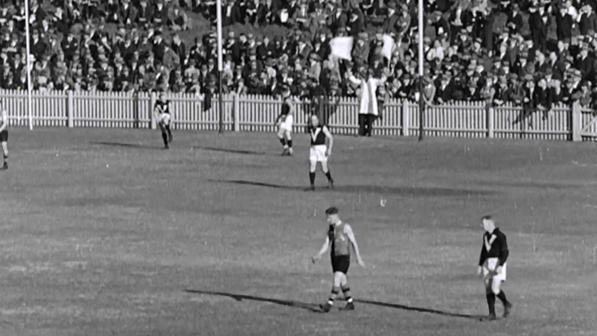 Black and white frame capture of the AFL goal umpire waving two flags signalling a six point score.