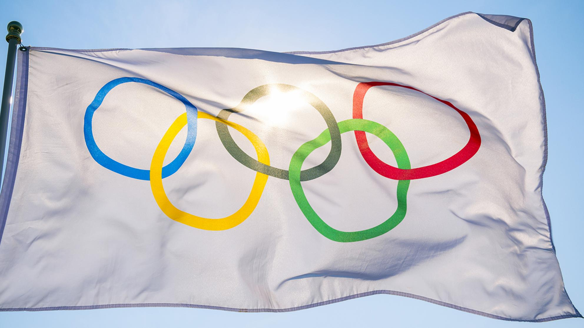The Olympic flag against a blue sky