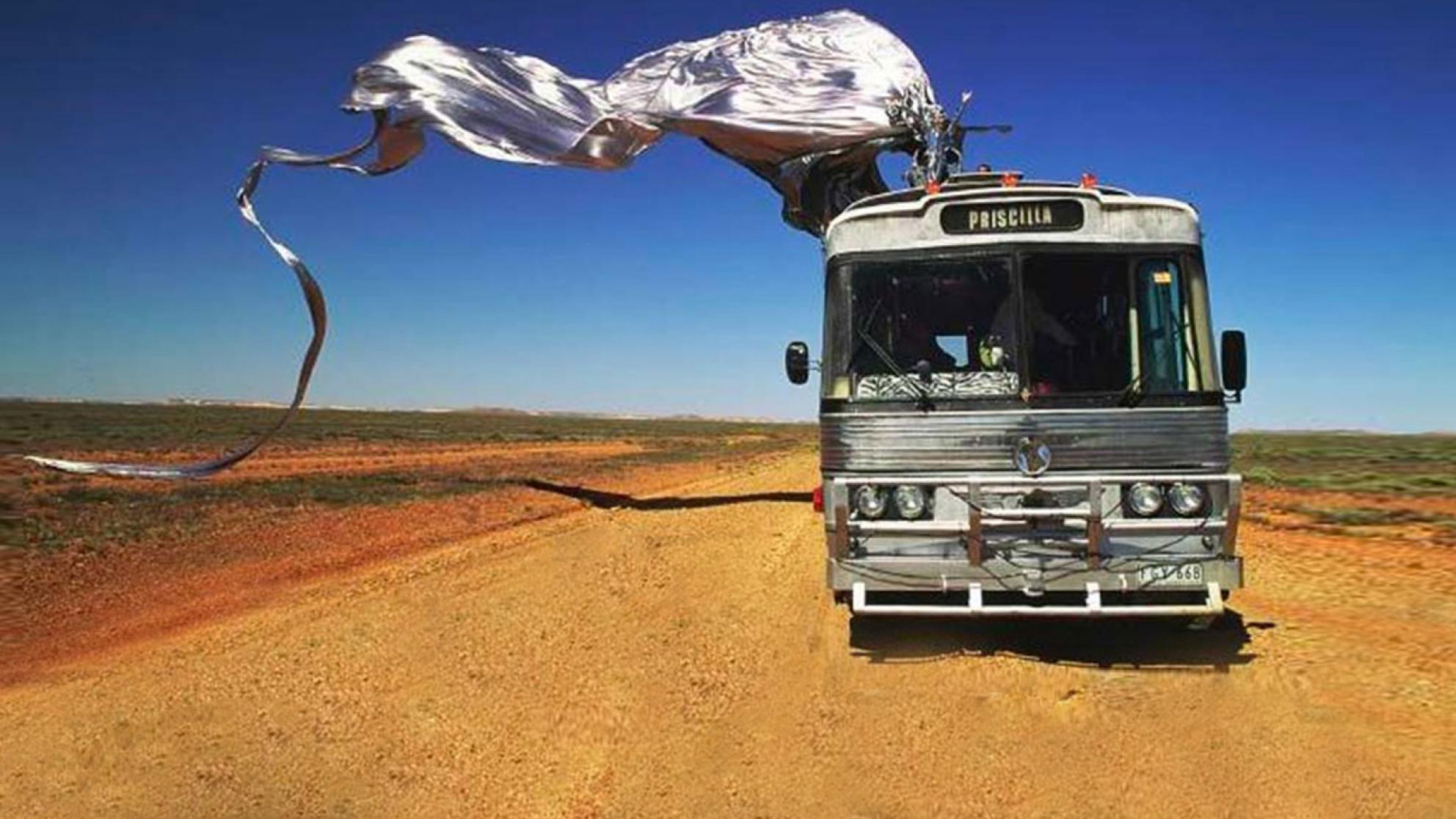 Scene from Priscilla, Queen of the Desert. A tour bus on a dirt road in the desert with blue sky in the background. On top of the bus is Guy Pearce in a shiny silver frock sitting on a giant stiletto shoe with a long train flowing behind the bus.