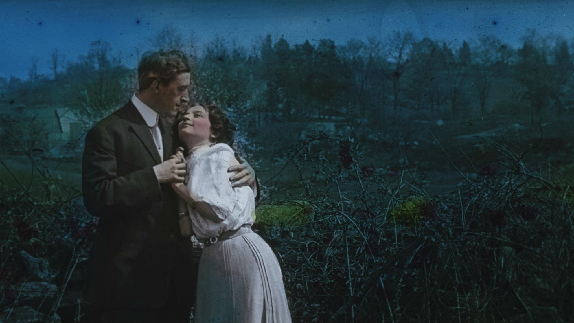 Glass slide image of a man and woman in an embrace standing in the moonlight, circa 1906.