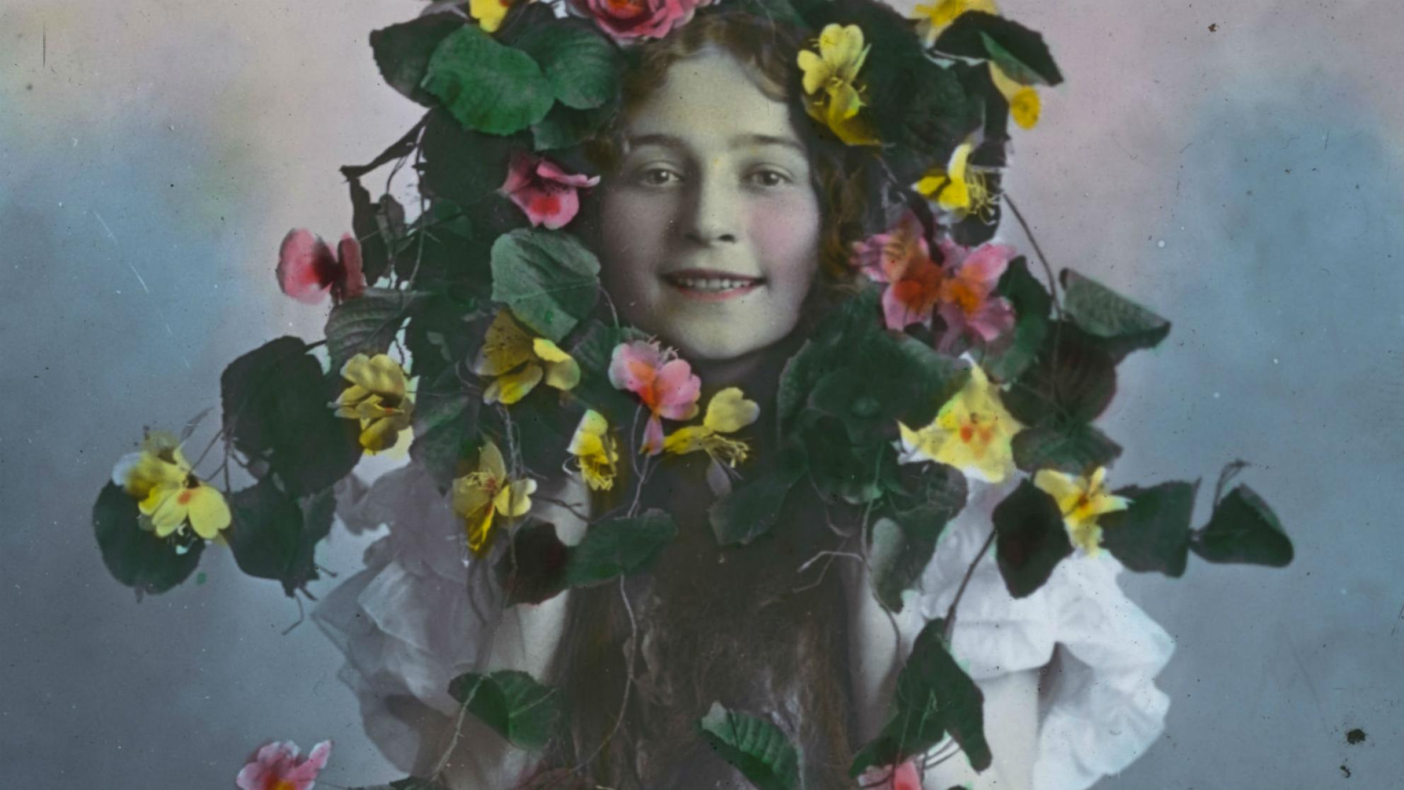 Glass slide image of a young girl peering through the centre of a wreath of flowers.