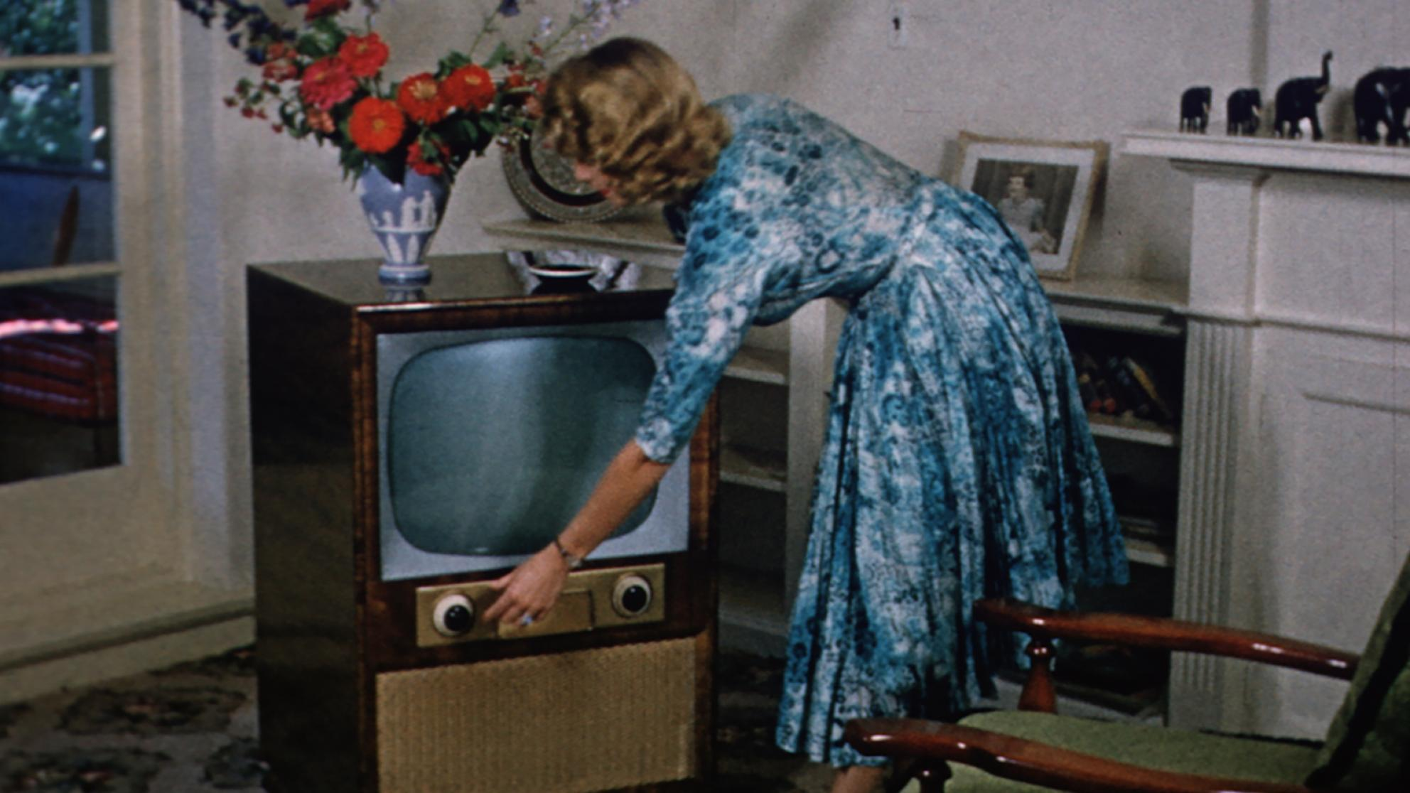 1950s image of a woman turning on a television set in her living room.