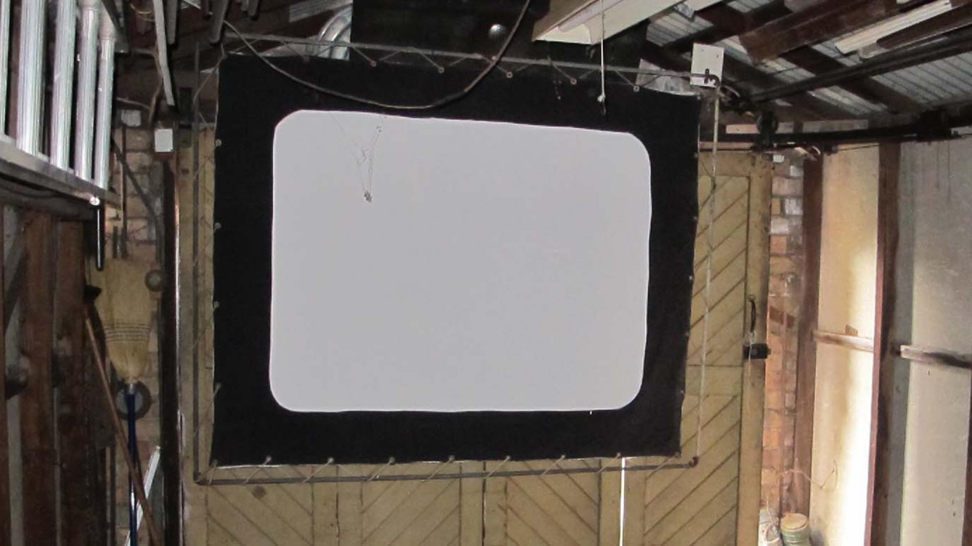 A screen hanging in a garage in Wollongong, part of the 1940s home cinema set-up of film projectionist Eddie Vormister