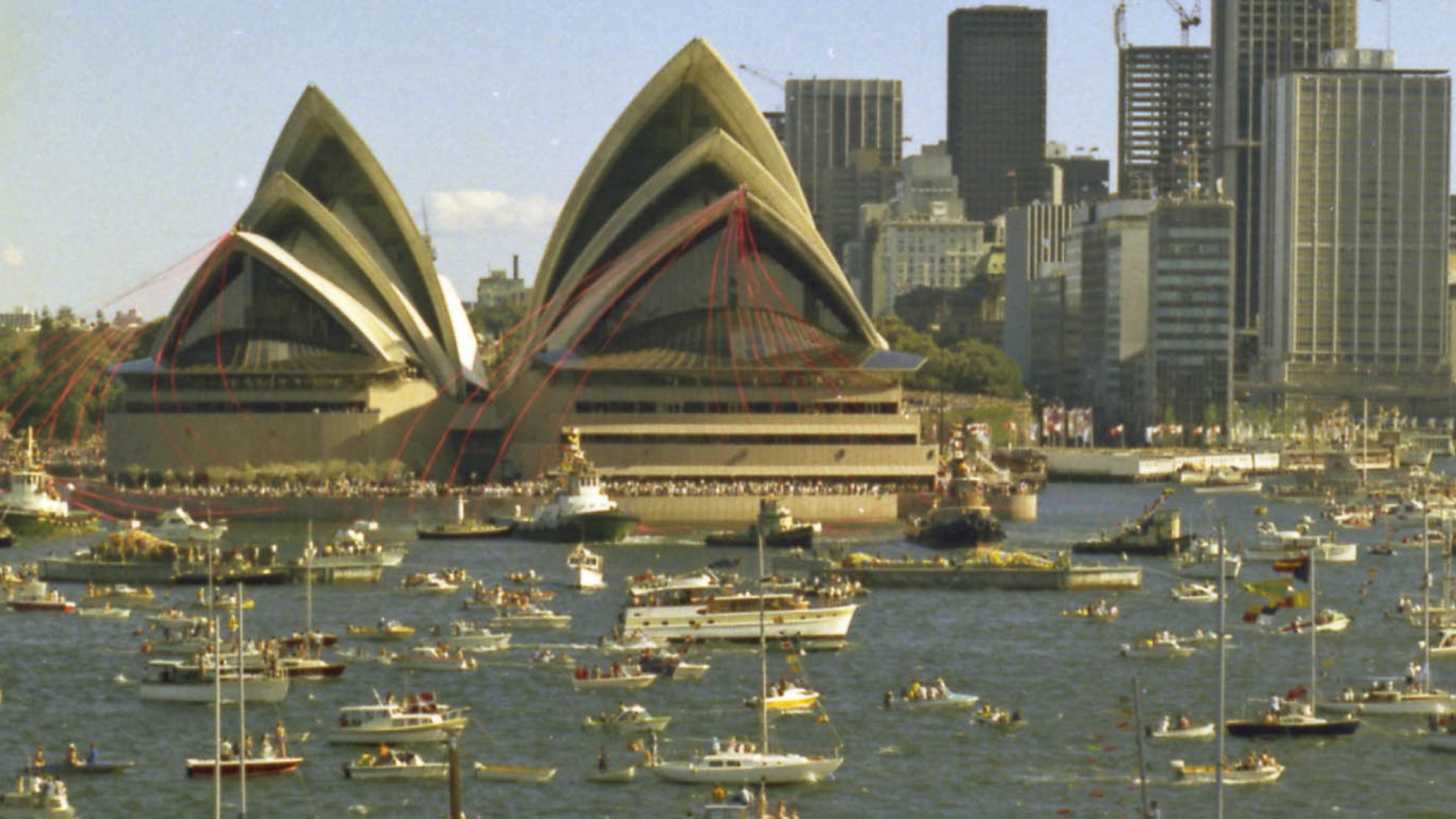 The Sydney Opera House is festooned with red ribbons. There are many boats on the water in front of it.