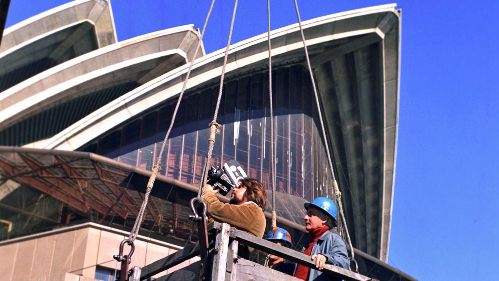 The sails of the Opera House tower above a camera operator and a man in a hardhat. They are standing in a wooden box which is hoisted to a crane.