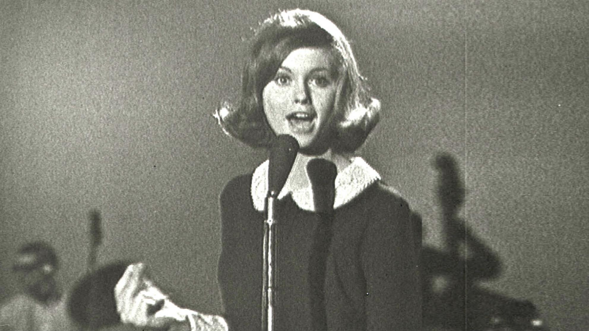 Olivia Newton-John at age 16 in a TV studio standing behind a microphone singing.