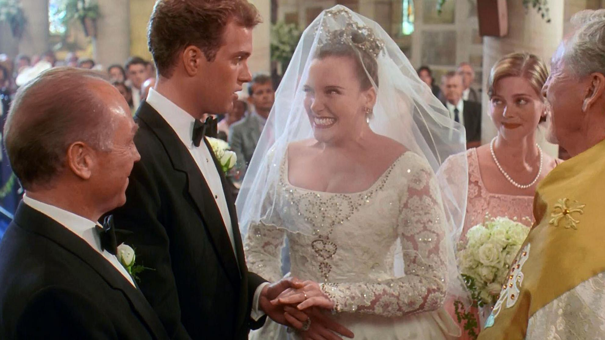 A scene from Muriel's Wedding where the main character, Muriel (Toni Collette) is getting married. She's standing at the alter with her groom, his best man, her bridesmaid and a minister.