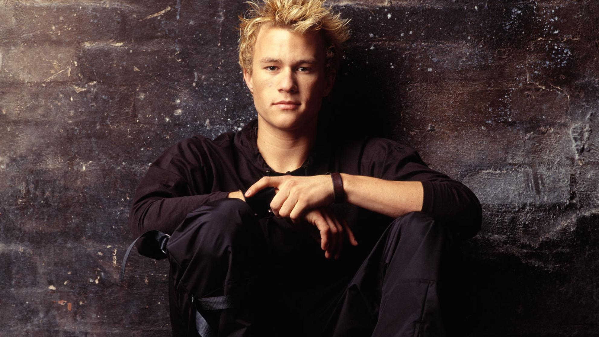 Heath Ledger is looking directly at the camera in a quietly confident pose. He is wearing black and up against a wall.